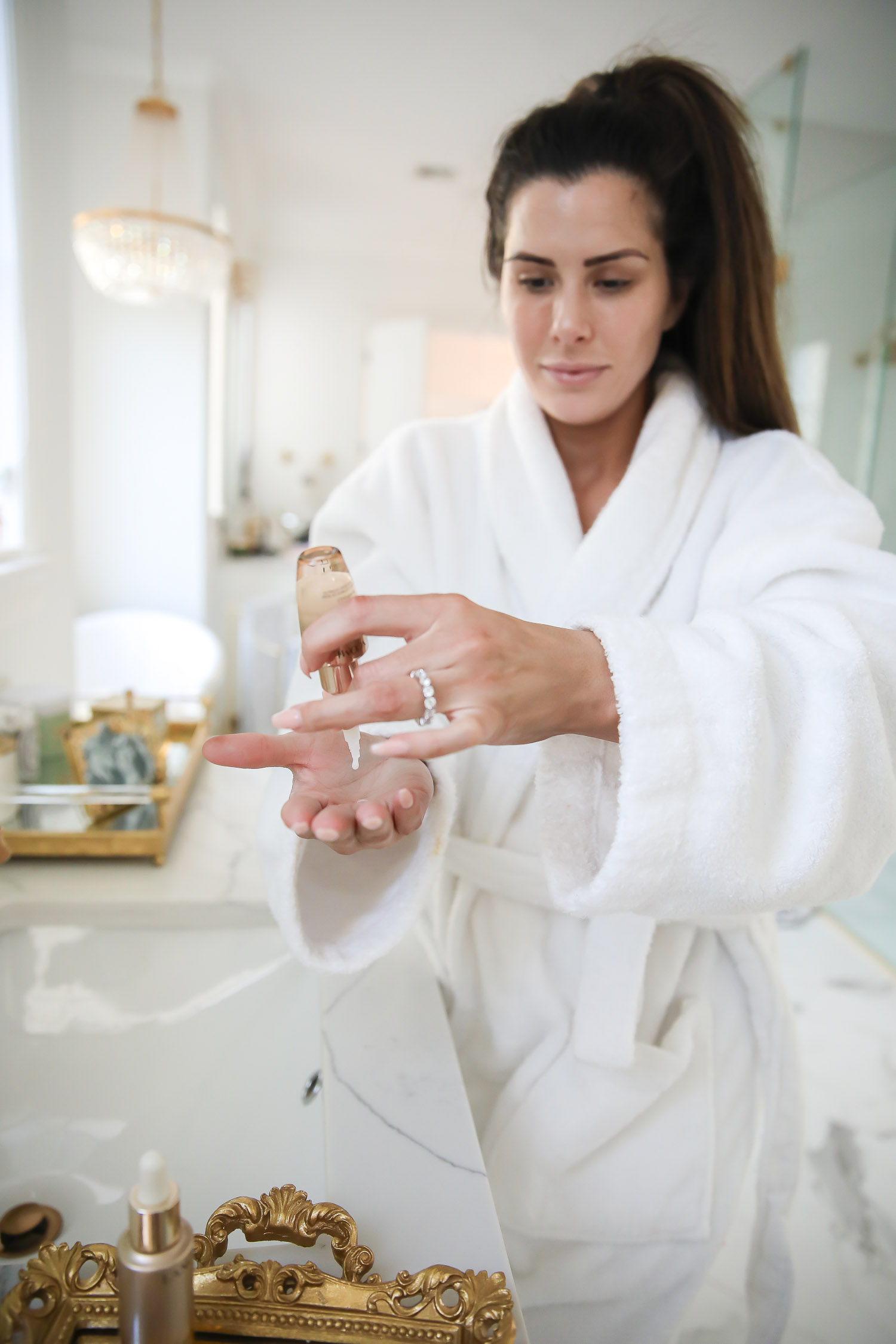 Lancome Skincare by popular US beauty blog, The Sweetest Thing: image of a woman using Lancome Absolue skincare products.