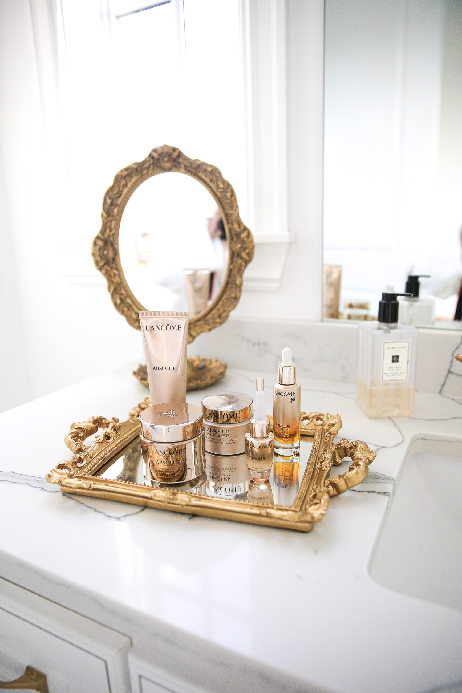 Lancome Skincare by popular US beauty blog, The Sweetest Thing: image of Lancome Absolue skincare products on a mirrored tray with gold handles.