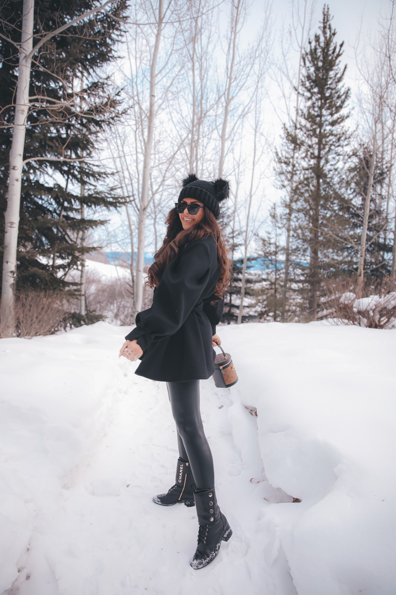 louis vuitton cannes bag, amazon cat eye sunglasses, pinterest winter fashion outfit ideas, emily gemma |Dressing Up by popular US fashion blog, The Sweetest Thing: image of Emily Gemma standing outside in the snow and wearing a Good American bodysuit, commando leggings, Chanel boots, Amazon sunglasses, Storets puff sleeve coat, Tasha double pom beanie, and holding a Louis Vuitton bag.