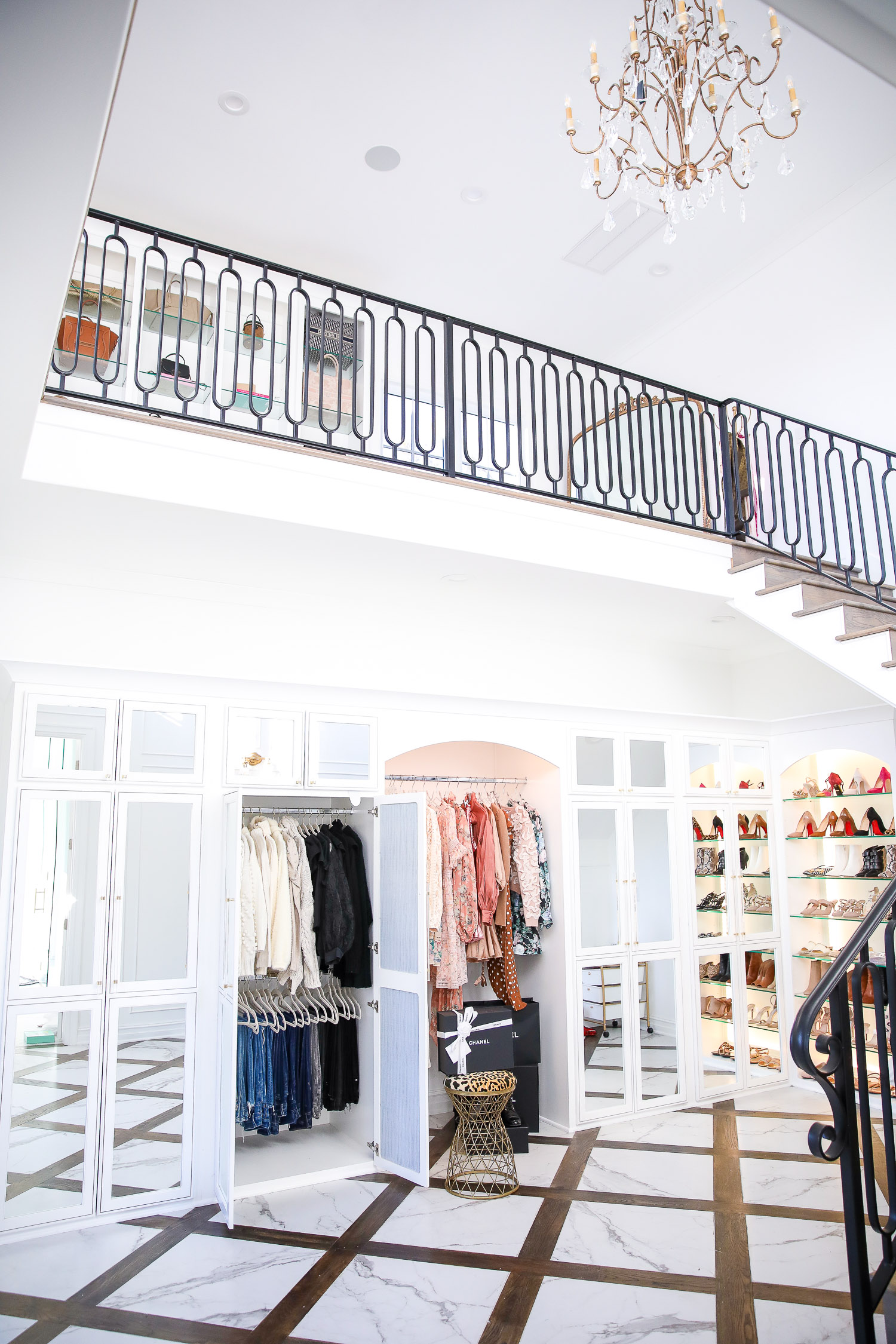 Top Picks by popular US life and style blog, The Sweetest Thing: image of a two story closet with marble and wood flooring, shoe display, full length mirrors, designer clothing and purses hanging from a clothing rack, grand stair case with a black metal railing, gold and crystal chandelier, and a pink velvet ottoman.
