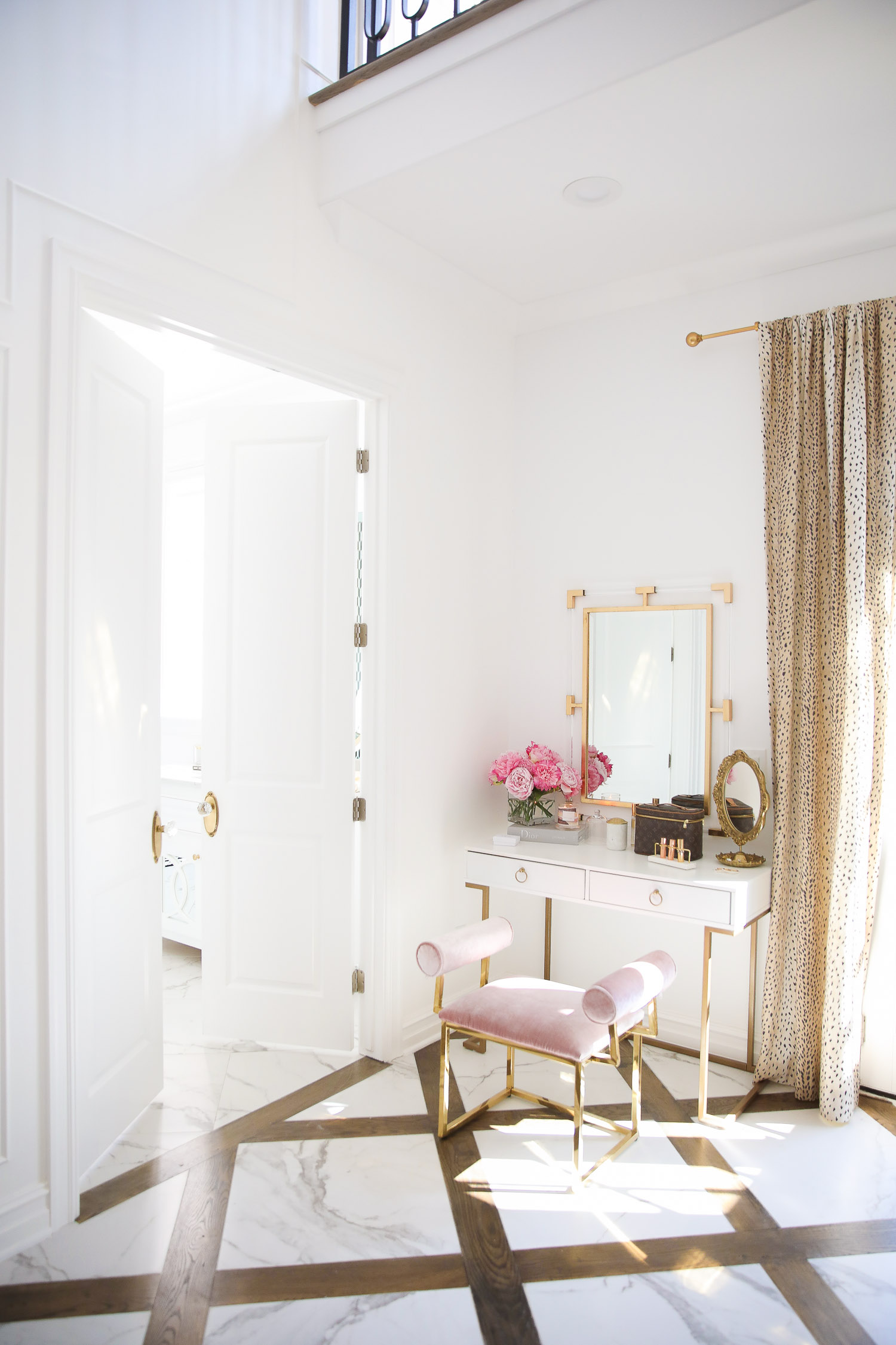 Top Picks by popular US life and style blog, The Sweetest Thing: image of a two story closet with marble and wood flooring, antelope print drapes, gold curtain rod, and a white and gold vanity with a pink velvet bench and gold and acrylic mirror.