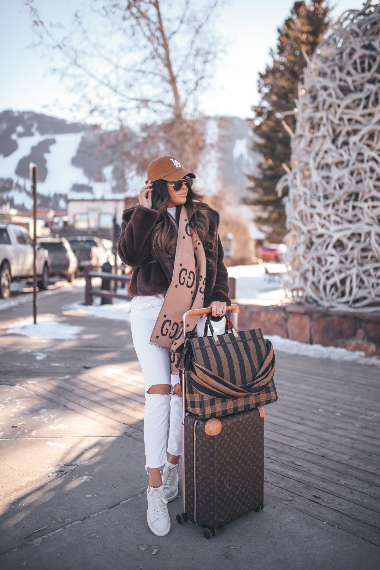 winter fashion outfit idea pinterest 2021, white denim in winter, louis vuitton horizon 55 carry on |Winter Fashion by popular US fashion blog, The Sweetest Thing: image of Emily Gemma standing outside in downtown Jackson Hole, WY and wearing a Free People top, BB Dakota faux fur jacket, distressed white denim jeans, Gucci scarf, '47 brand cap, Le Specs sunglasses, and standing next to a Louis Vuitton rolling suitcase and holding a Fendi tote bag.
