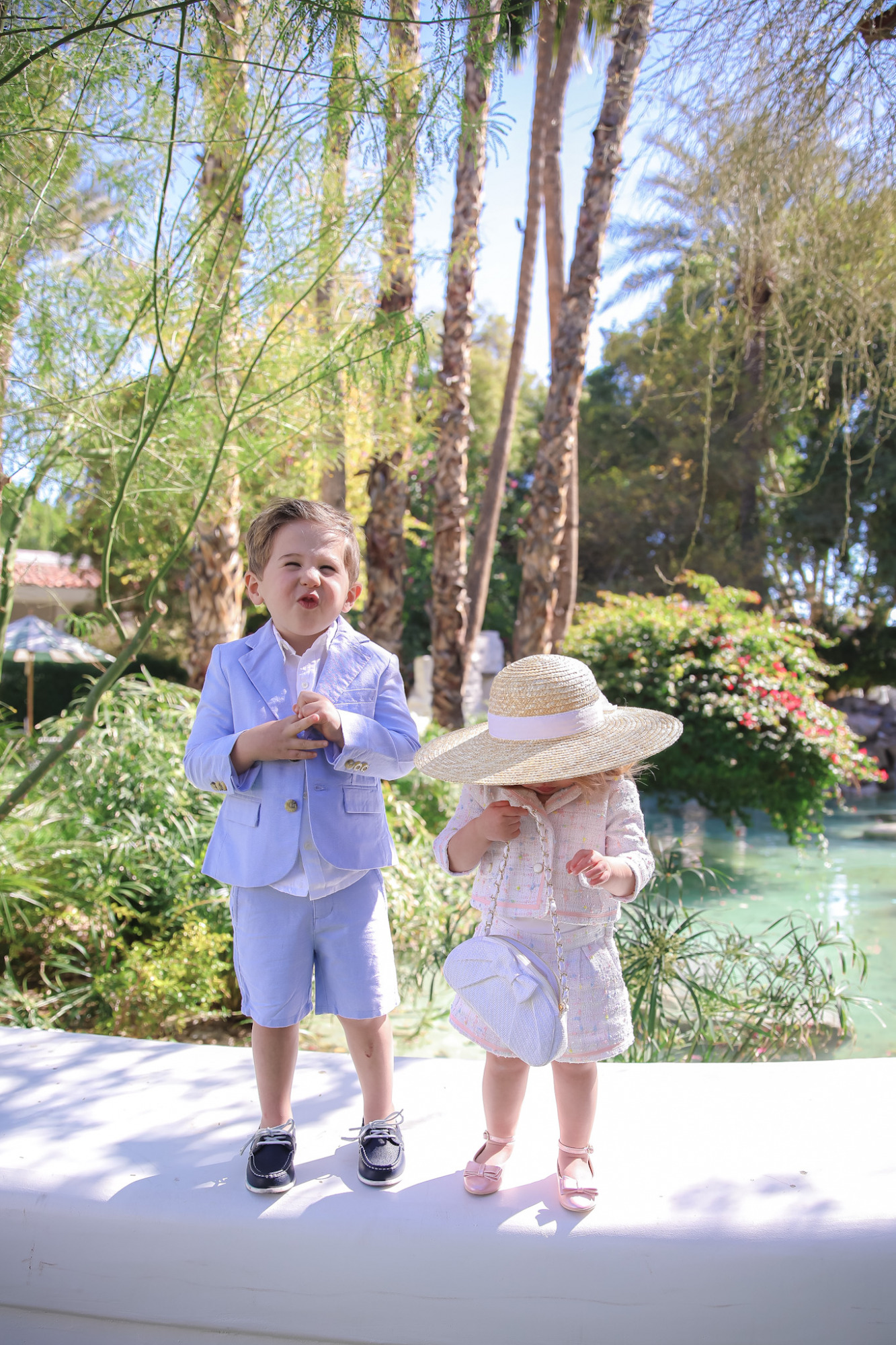 Spring Outfit Ideas for Kids by popular US fashion blog, The Sweetest Thing: image of a young boy and girl standing outside next to a landscaped pond and wearing aPink Boucle Jacket, Pink Boucle Shorts, Pink Bow Flats, White Purse, Straw Sun Hat, Seersucker Blazer, Seersucker Shorts, White Button-down, and Leather Boat Shoes.