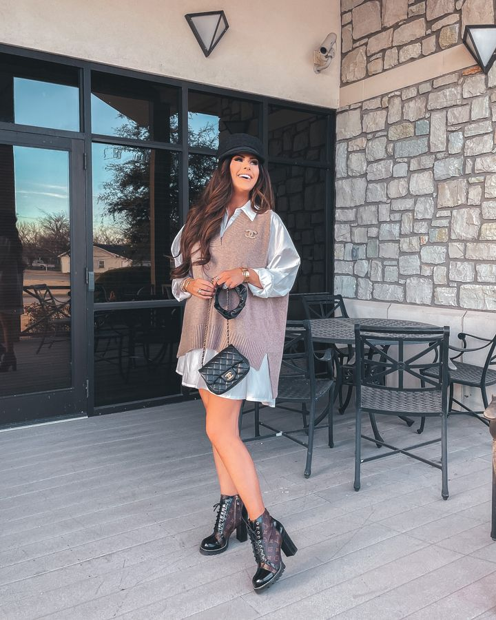 Chanel small flap bag romance with ruffle strap, Louis Vuitton star trail ankle boots, oversized t-shirt, Chanel brooch, Chanel cap, Oversized sweater vest, Emily gemma Pinterest outfit ideas