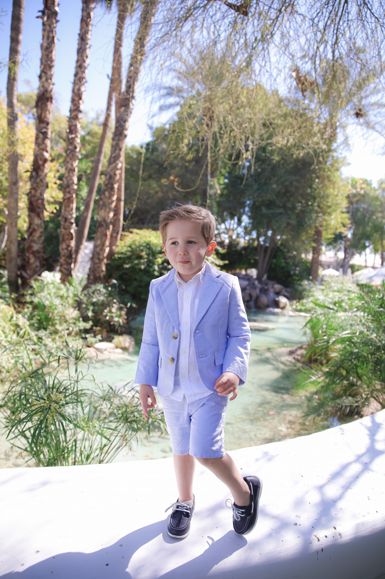 janie and jack easter kids outfits 2021, kids easter outfit ideas toddler, emily gemma, scottsdale fashion blog4 |Spring Outfit Ideas for Kids by popular US fashion blog, The Sweetest Thing: image of a young boy standing outside next to a landscaped pond and wearing a Seersucker Blazer, Seersucker Shorts, White Button-down, and Leather Boat Shoes.