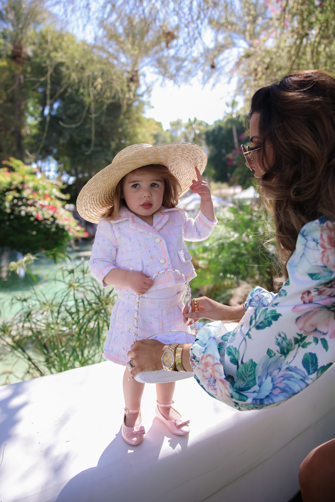 janie and jack easter kids outfits 2021, kids easter outfit ideas toddler, emily gemma, scottsdale fashion blog4 |Spring Outfit Ideas for Kids by popular US fashion blog, The Sweetest Thing: image of a young girl standing outside next to a landscaped pond and wearing aPink Boucle Jacket, Pink Boucle Shorts, Pink Bow Flats, White Purse, and Straw Sun Hat.