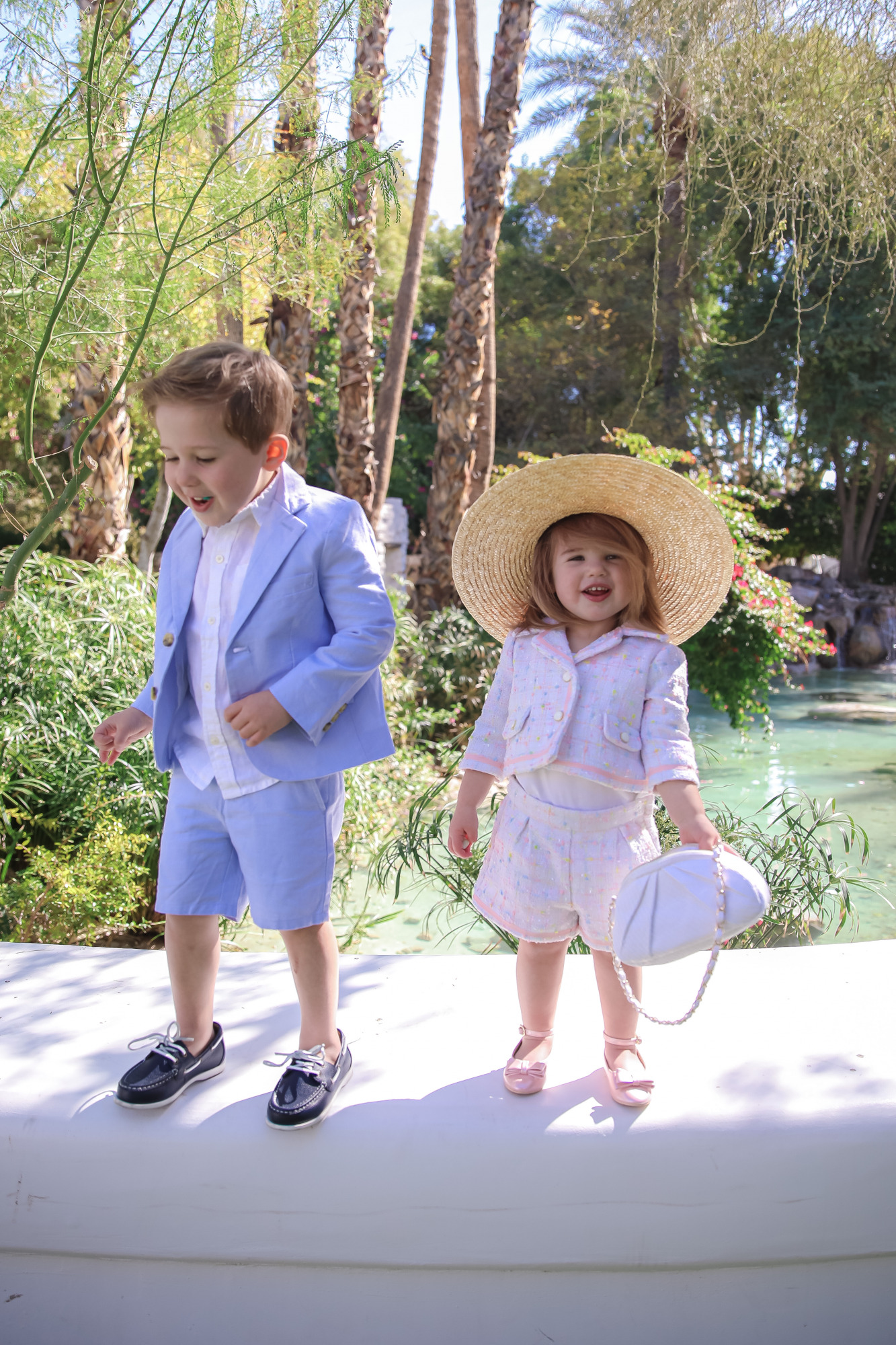 janie and jack easter kids outfits 2021, kids easter outfit ideas toddler, emily gemma, scottsdale fashion blog4 |Spring Outfit Ideas for Kids by popular US fashion blog, The Sweetest Thing: image of a young boy and girl standing outside next to a landscaped pond and wearing aPink Boucle Jacket, Pink Boucle Shorts, Pink Bow Flats, White Purse, Straw Sun Hat, Seersucker Blazer, Seersucker Shorts, White Button-down, and Leather Boat Shoes.