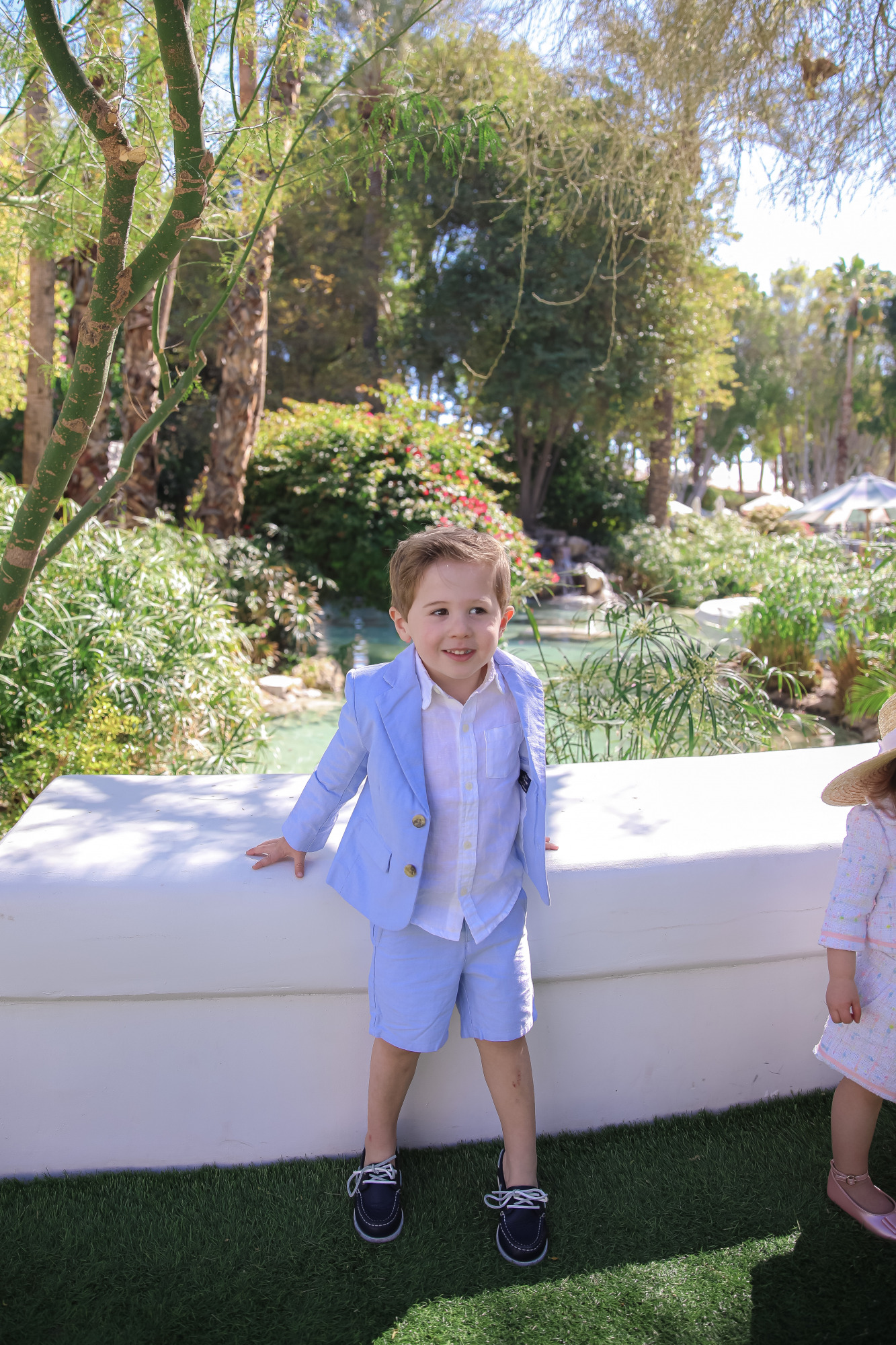 janie and jack easter kids outfits 2021, kids easter outfit ideas toddler, emily gemma, scottsdale fashion blog9 |Spring Outfit Ideas for Kids by popular US fashion blog, The Sweetest Thing: image of a young boy and girl standing outside next to a landscaped pond and wearing aPink Boucle Jacket, Pink Boucle Shorts, Pink Bow Flats, White Purse, Straw Sun Hat, Seersucker Blazer, Seersucker Shorts, White Button-down, and Leather Boat Shoes.