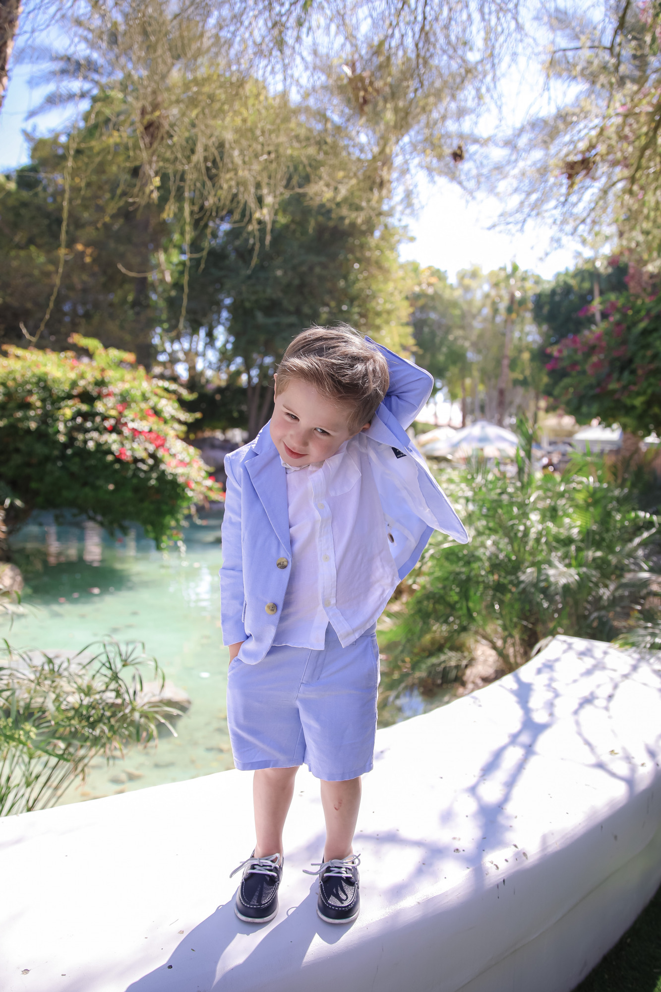 janie and jack easter kids outfits 2021, kids easter outfit ideas toddler, toddler boy seersucker suit |Spring Outfit Ideas for Kids by popular US fashion blog, The Sweetest Thing: image of a young boy standing outside next to a landscaped pond and wearing a Seersucker Blazer, Seersucker Shorts, White Button-down, and Leather Boat Shoes.