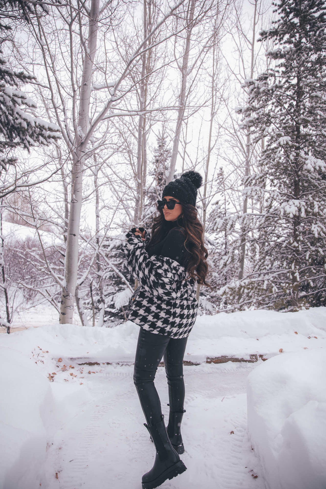 lug sole boots chelsea boots, winter outfit idea snow jackson hole, emily gemma | Lug Sole Boots by popular US fashion blog, The Sweetest Thing: image of Emily Gemma wearing a Storets black and white houndstooth jacket, Good American bodysuit, BlankNYC faux leather pants, Steve Madden black lug sole boots, BP. sunglasses, TopShop black pom beanie, Chanel handbag, Monica Vinader ring, Rolex watch, Cartier bracelets, and Iconic Nude' + KIM K.W. + White Russian Sparkle lip combo.