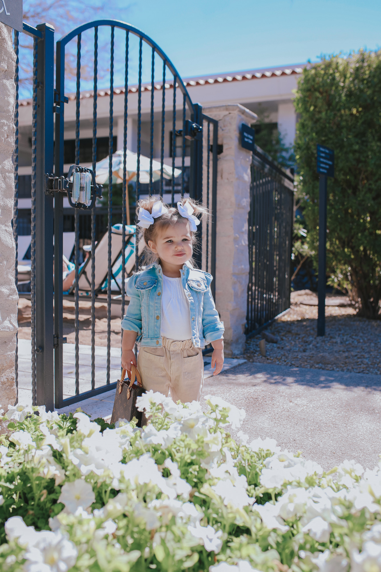 Mom Jeans by popular US fashion blog, The Sweetest Thing: image of a little girl standing by a wrought iron gate in Scottsdale, Arizona and wearing two white hair bows, jean jacket, white shirt, tan pants and holding a mini Louis Vuitton purse.