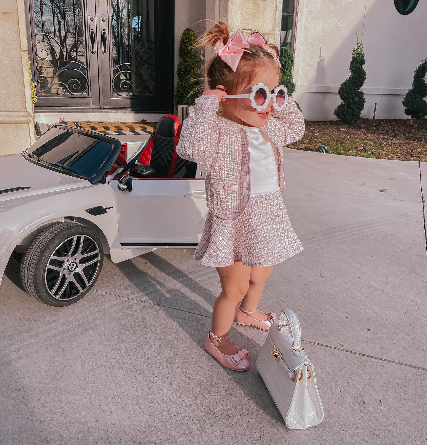 Gemma Gang, Best Toy Cars for Kids, Little Girl Preppy Outfit, Little Girl Sunglasses, Bows for Little Girls, Baby Birkin |Instagram Recap by popular US fashion blog, The Sweetest Thing: image of a little girl standing next to a battery powered Bentley and baby Birkin bag while wearing a pink tweed skirt suit, pink box, white shirt, and white flower frame sunglasses.