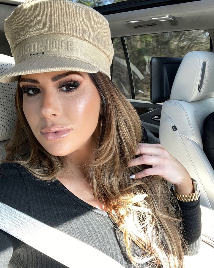 Emily Gemma Makeup Routine, Best Foundation, Best Makeup for Problem Skin, Emily Gemma Lip Combo, Dior Hat, Best Mascara 2021, Best Foundation 2021 |Instagram Recap by popular US fashion blog, The Sweetest Thing: image of Emily Gemma sitting in a car and wearing a black Good American top, Christian Dior hat, and Rolex watch.