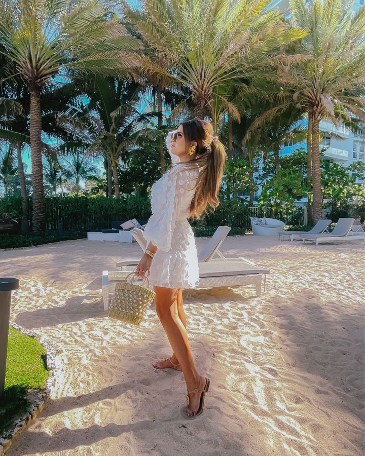 Emily Ann Gemma, Summer Style, Beach Style, What to wear to the beach, Bachelorette Dress Ideas, Bridal Shower Outfit Ideas, Bridal Shower Dress, Rehearsal Dinner Dress, White Dress, Summer Style, Easter Dress |Instagram Recap by popular US fashion blog, The Sweetest Thing: image of Emily Gemma standing on a beach next to some palm trees and wearing a white mini dress and brown strap sandals.
