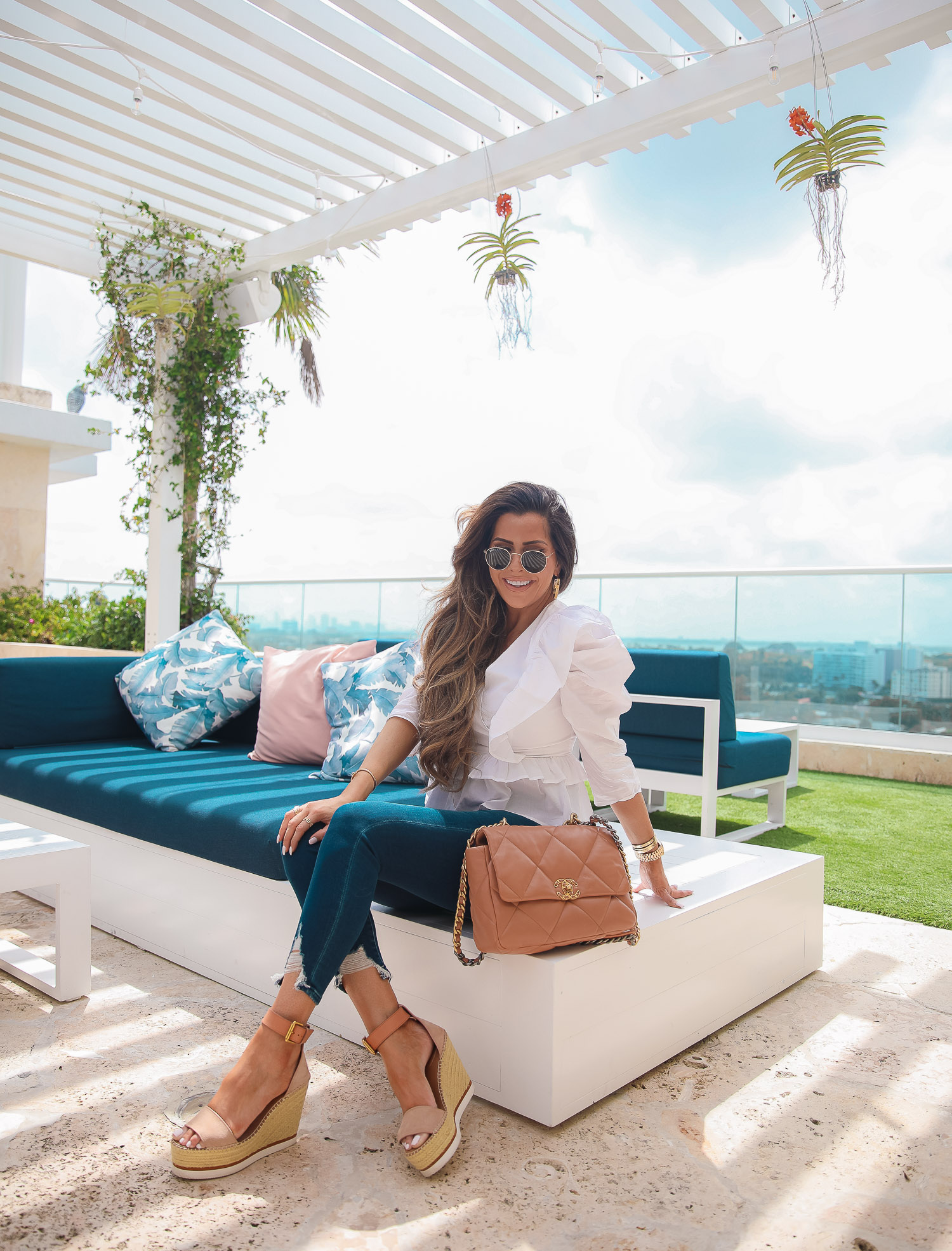 EXPRESS spring fashion, good american jean dupes, chanel 19 medium tan carmel color, emily gemma, the grand miami surfside |Instagram Recap by popular US fashion blog, The Sweetest Thing: image of Emily Gemma sitting outside and wearing a white Express top, Express jeans, and tan strap espadrilles.