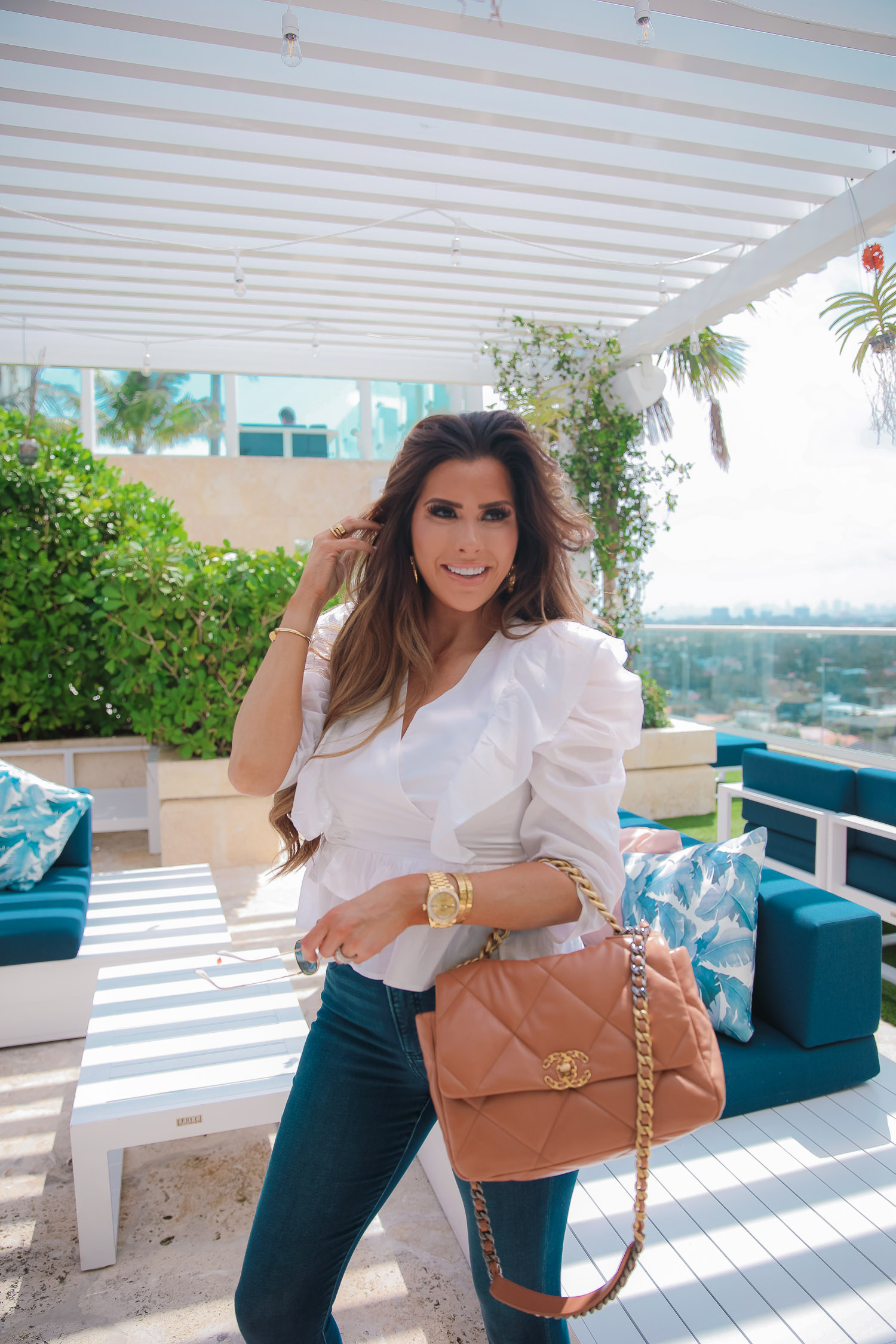 EXPRESS spring fashion, good american jean dupes, chanel 19 medium tan carmel color, emily gemma, the grand miami surfside   Spring Fashion by popular US fashion blog, The Sweetest Thing: image of Emily Gemma wearing a Express white white ruffle and puff sleeve top, Express Jeans, Espadrille sandals, and holding a Chanel 19 bag.