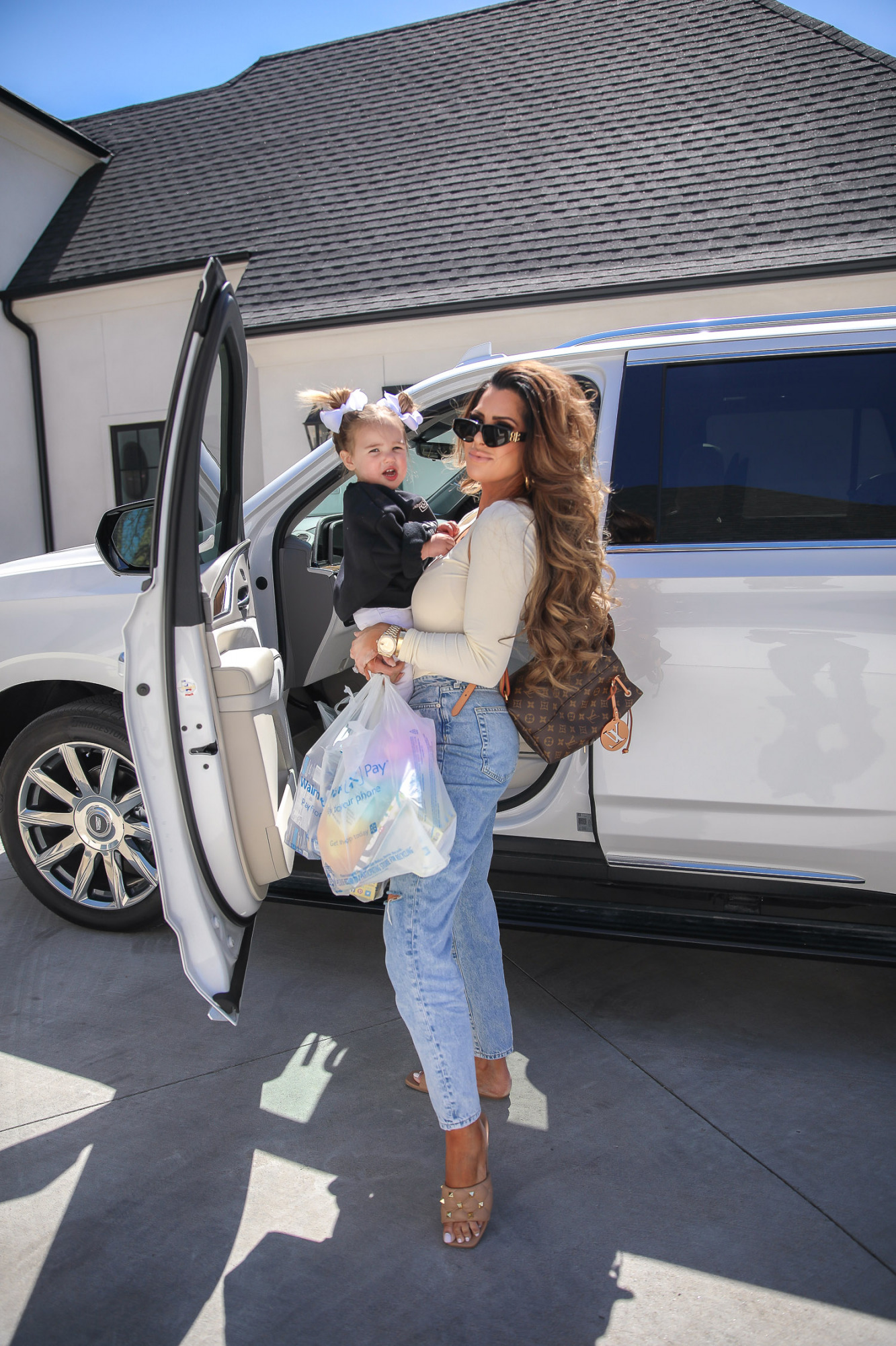 2021 escalade, best high waisted mom jeans, H&M mom jeans, Kell parker sandals, Balenciaga sunglasses, walmart delivery and pick up details, emily gemma-21 | Instagram Recap by popular US fashion blog, The Sweetest Thing: image of Emily Gemma holding her young daughter next to their white SUV and holding some Walmart shopping bags.