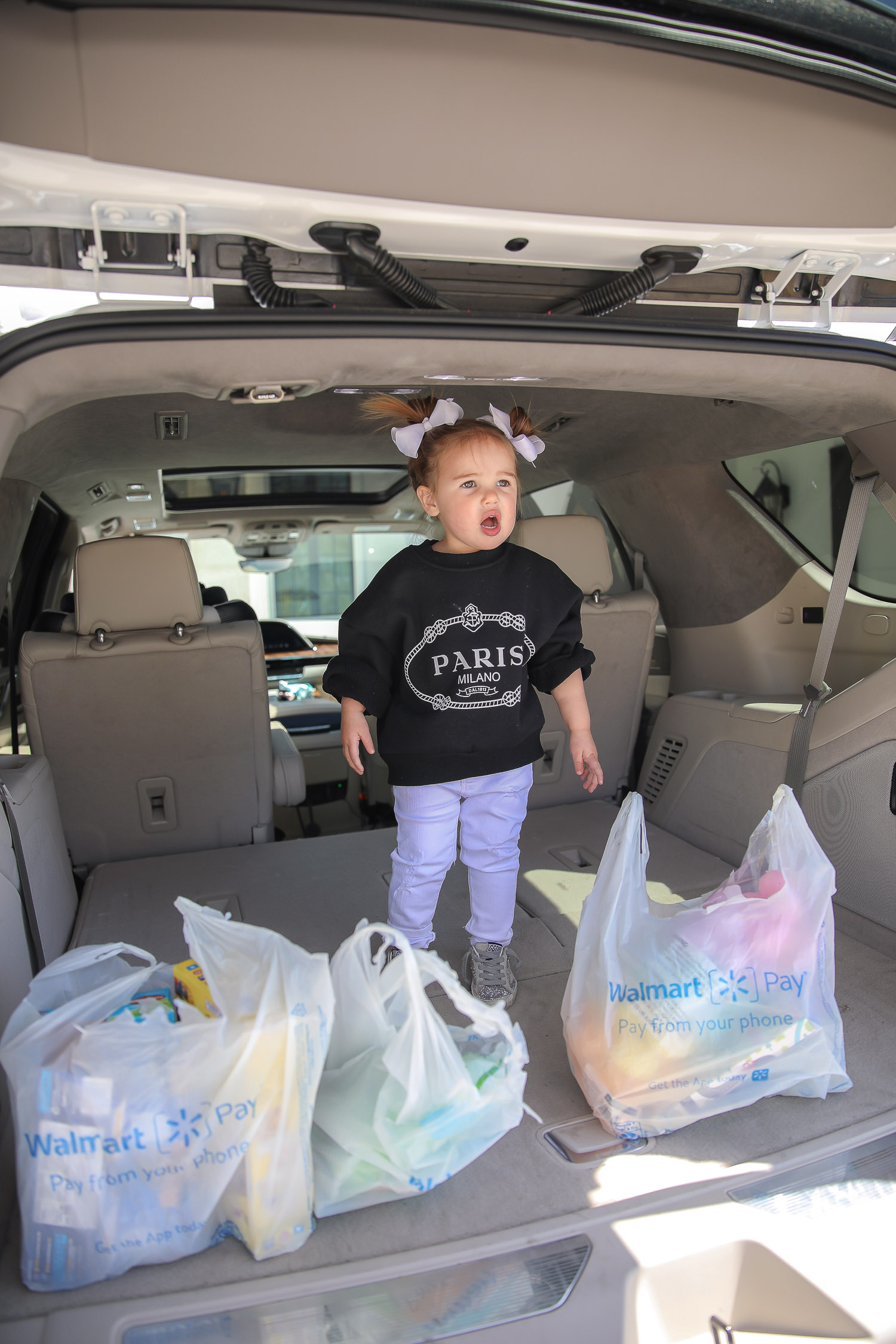 Easter Basket Ideas by popular US lifestyle blog, The Sweetest Thing: image of a little girl wearing a black Paris sweatshirt, white jeans, and white hair bows standing next to some Walmart shopping bags in the back of a White SUV.