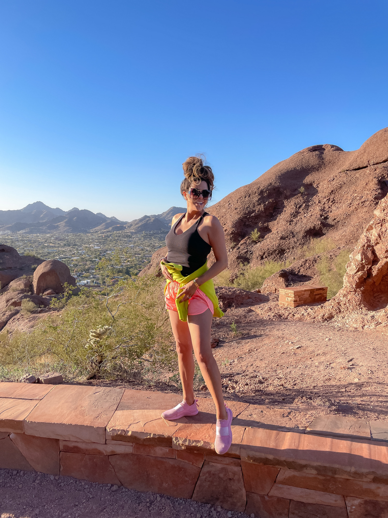 free people shorts, best workout gear spring 2021, camelback mountain, alo yoga top, emily gemma12 |Hiking Outfits by popular US fashion blog, The Sweetest Thing: image of Emily Gemma wearing a Alo yoga top, Nike half zipper pullover sweatshirt, Free People shorts, APL sneakers and Amazon sunglasses while standing out a low rock wall.