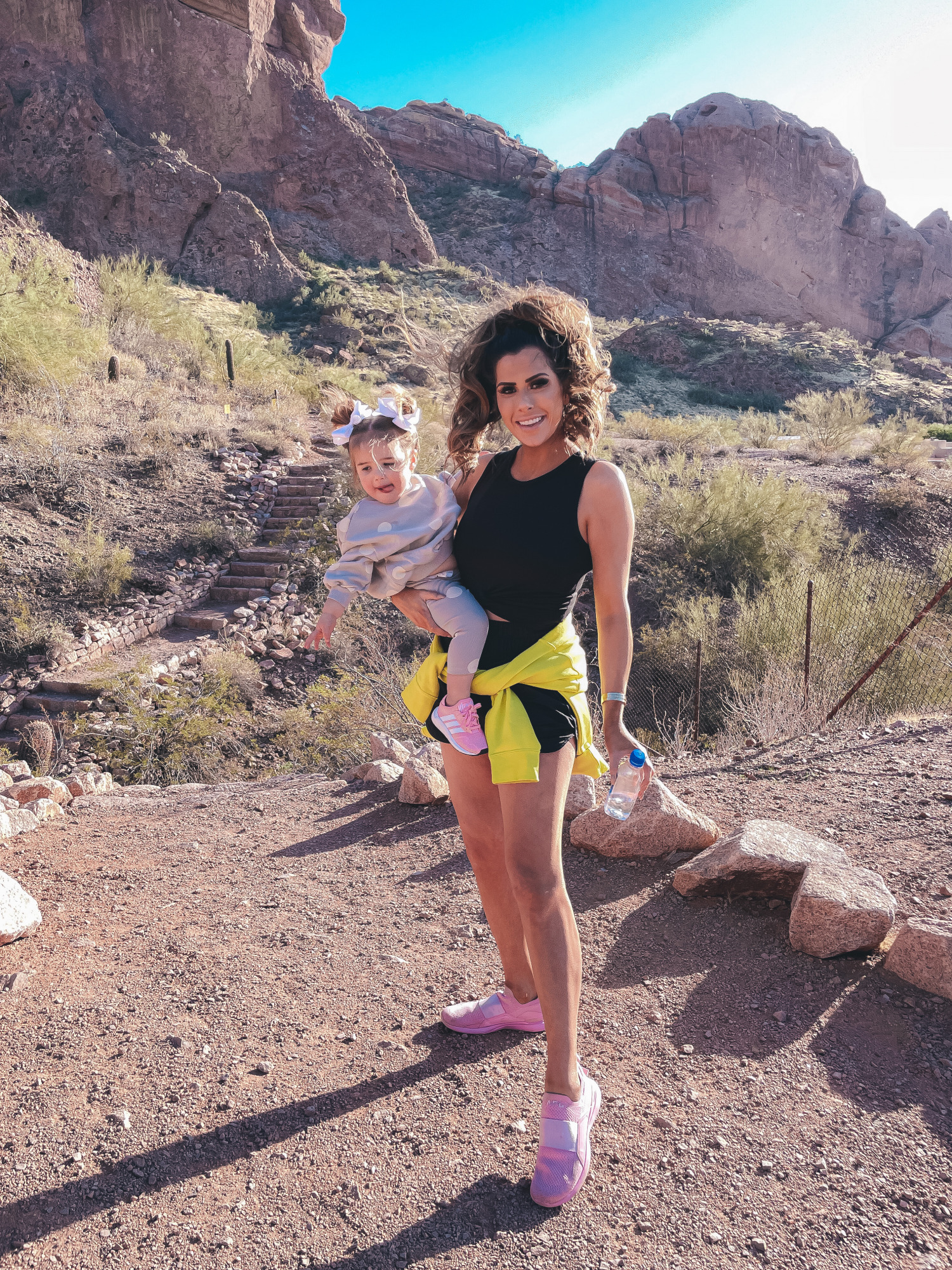 free people shorts, best workout gear spring 2021, camelback mountain, alo yoga top, emily gemma12 |Hiking Outfits by popular US fashion blog, The Sweetest Thing: image of Emily Gemma wearing a Alo yoga top, Nike half zipper pullover sweatshirt, Free People shorts, APL sneakers and Amazon sunglasses while holding her daughter Sophie who's wearing a grey and white polka dot lounge set, sneakers, and matching white hair bows.