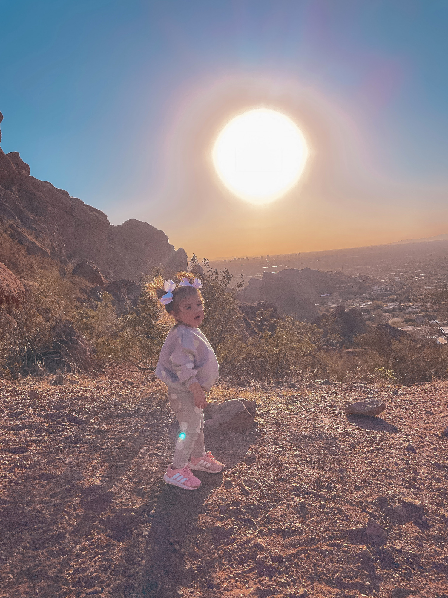 Hiking Outfits by popular US fashion blog, The Sweetest Thing: image of a little girl standing outside and wearing a grey and white polka dot lounge set, sneakers, and matching white hair bows.