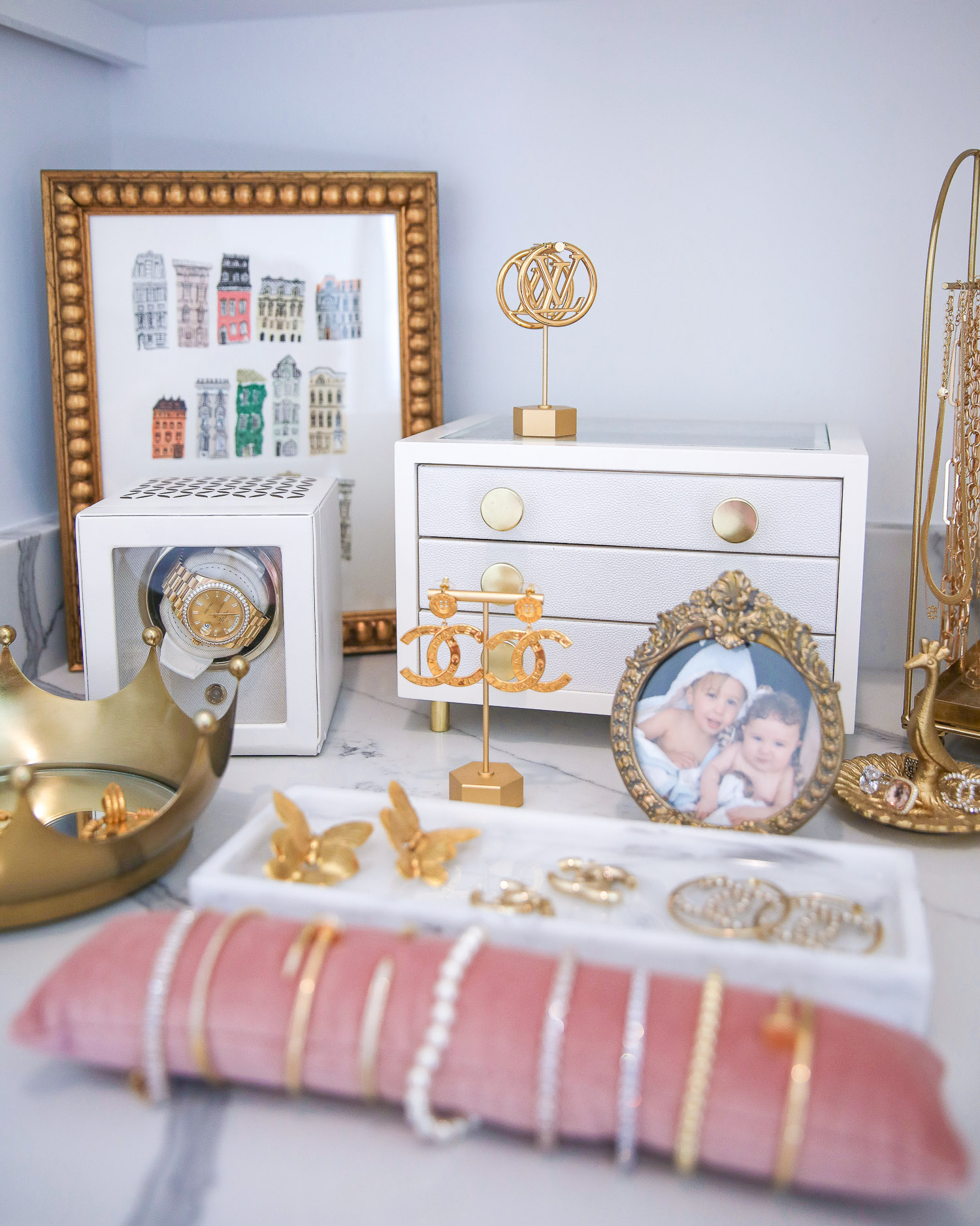 Amazon Must Haves by popular US life and style blog, The Sweetest Thing: image of gold picture frames, gold jewelry holders, white jewelry box, pink velvet bracelet cushion, and gold necklace holder on a white marble counter top.