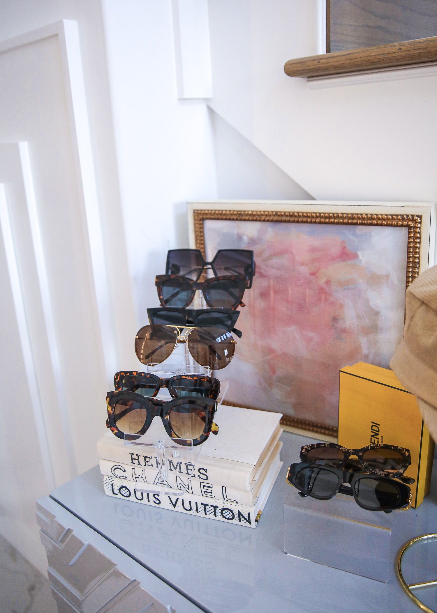 Amazon home decor sunglasses display, acrylic sunglasses display, best amazon sunglasses summer 2021, Emily Gemma |Amazon Must Haves by popular US life and style blog, The Sweetest Thing: image of a orange Hermes tray filled with gold earring stands, Louis Vuitton jewelry, and a glass dish filled with mints, sunglasses on an acrylic sunglasses stand, and Christian Dior hat on a gold hat stand.