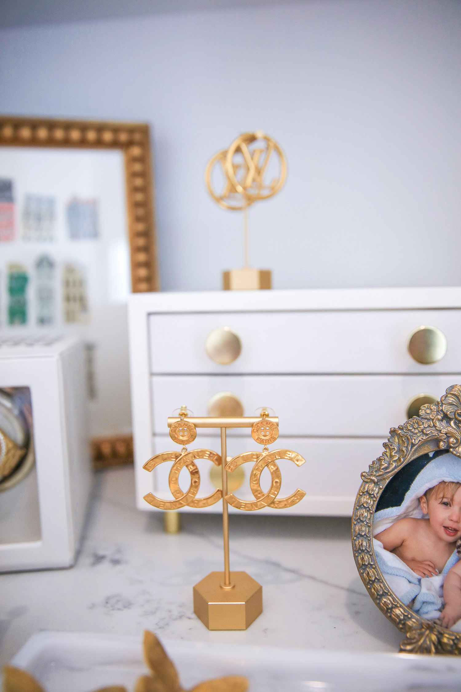 Amazon must haves jewelry holder, gold earring stands amazon, Emily Gemma amazon store, Chanel gold button earrings spring 2021, designer jewelry collection |Amazon Must Haves by popular US life and style blog, The Sweetest Thing: image of gold picture frames, gold jewelry holders, white jewelry box, pink velvet bracelet cushion, Chanel Gold button collection earrings on a gold earring stand, and gold necklace holder on a white marble counter top.