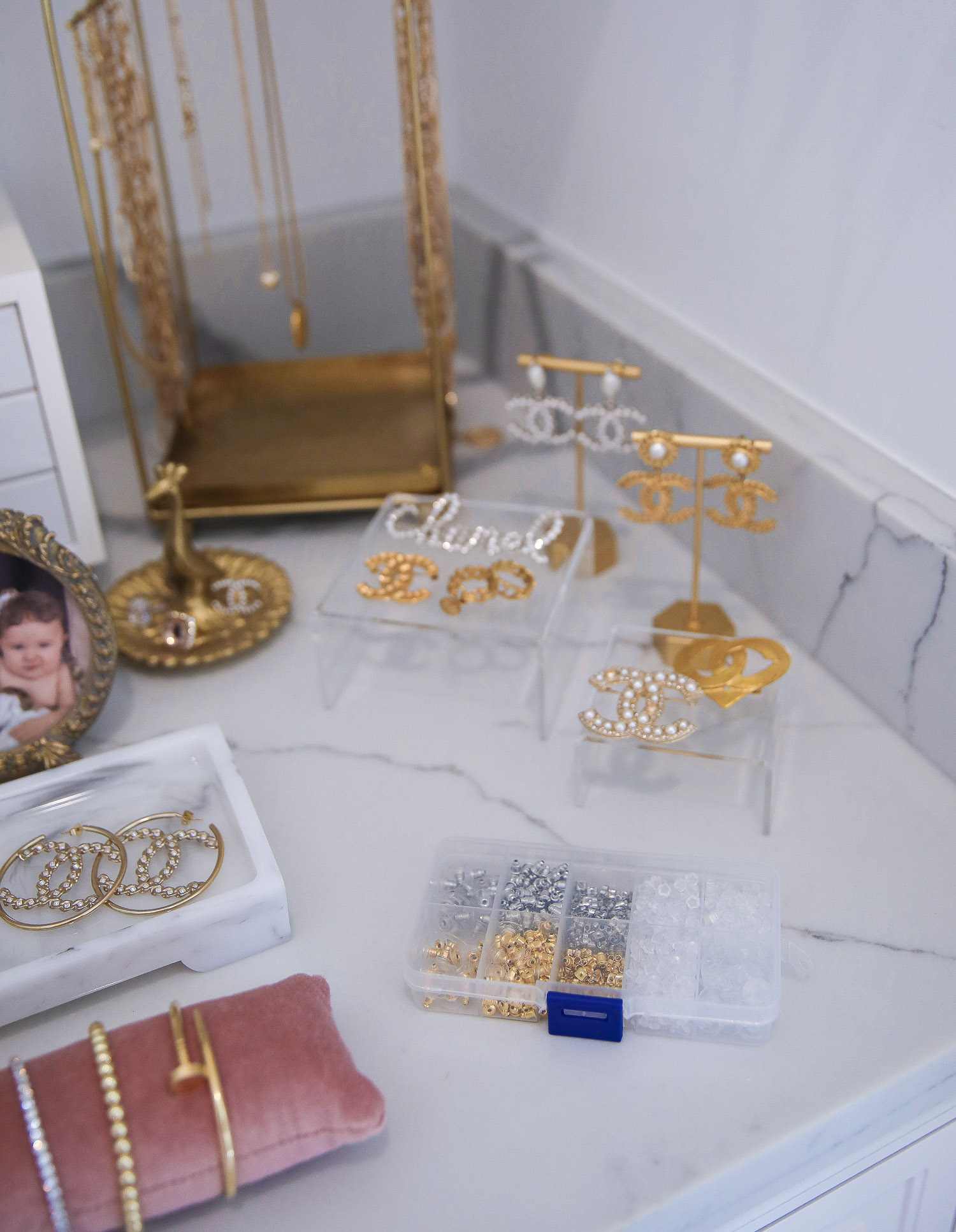 amazon earring backs, Chanel earrings 2021, amazon must haves Emily Gemma |Amazon Must Haves by popular US life and style blog, The Sweetest Thing: image of gold picture frames, gold jewelry holders, white jewelry box, pink velvet bracelet cushion, earring backs in a storage container, and gold necklace holder on a white marble counter top.