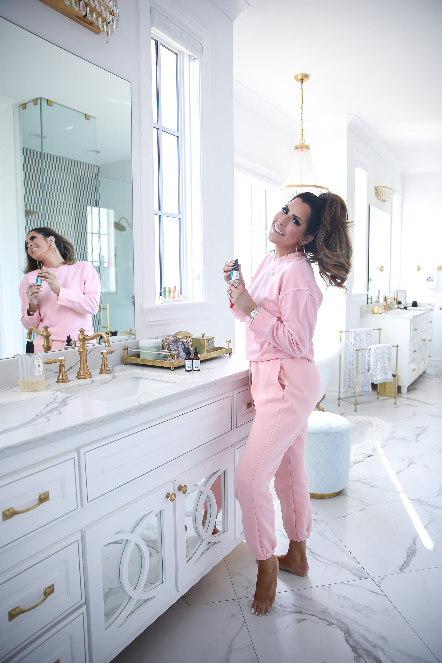 Skinceuticals CE Ferulic SilyMarin Phloretin CF, best Vitamim C serum, CE Ferulic vs Phloretin CF, why do you need Vitamin C, emily gemma skincare | Vitamin C Skincare by popular beauty blog, The Sweetest Thing: image of Emily Gemma standing in her bathroom and wearing a pink sweatsuit while holding a bottle SkinCeuticals skin care product.