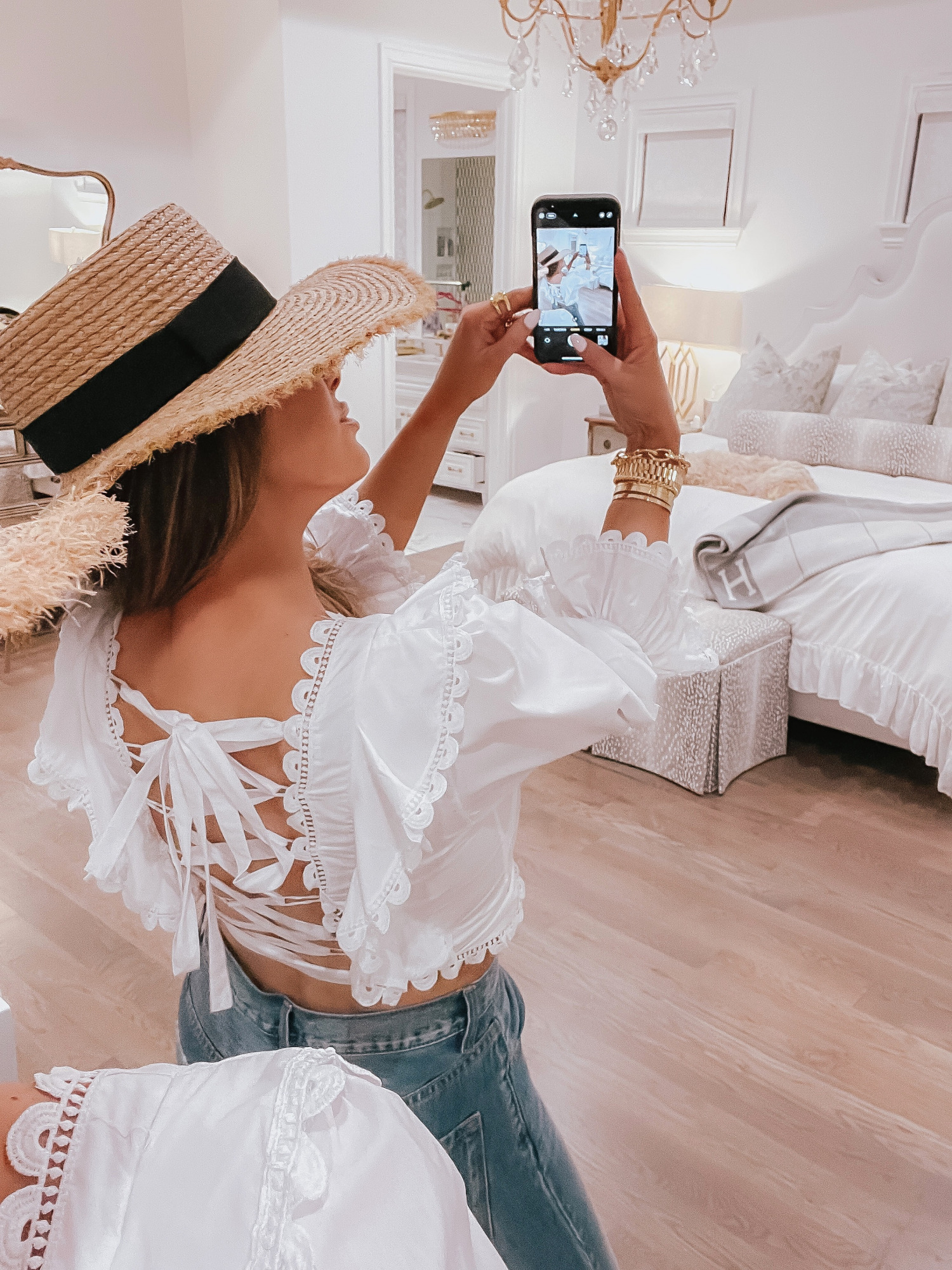 Vici Try On by popular US fashion blog, The Sweetest Thing: image of Emily Gemma wearing a white corset back crop top, jeans, and straw sun hat.