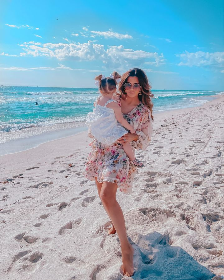 Floral Zimmermann Dress, Emily Gemma, Family Beach Photo, Emily Gemma, Dior Sunglasses, Chanel Earrings, Emily Ann Gemma   April Instagram Recap by popular US fashion blog, The Sweetest Thing: image of Emily Gemma holding her daughter Sophie on the beach and wearing a white floral print dress, gold Chanel earrings and floral print mini dress with long sleeves.