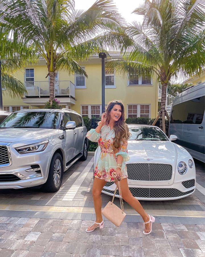 Palm Beach, Pink Chanel, Chanel Handbag, White Bentley, Zimmerman Outfit, Floral Shorts and Top, Emily Gemma \ April Instagram Recap by popular US fashion blog, The Sweetest Thing: image of Emily Gemma standing in front of a white Bentley and wearing a blue floral print romper and pink strap block heel sandals.