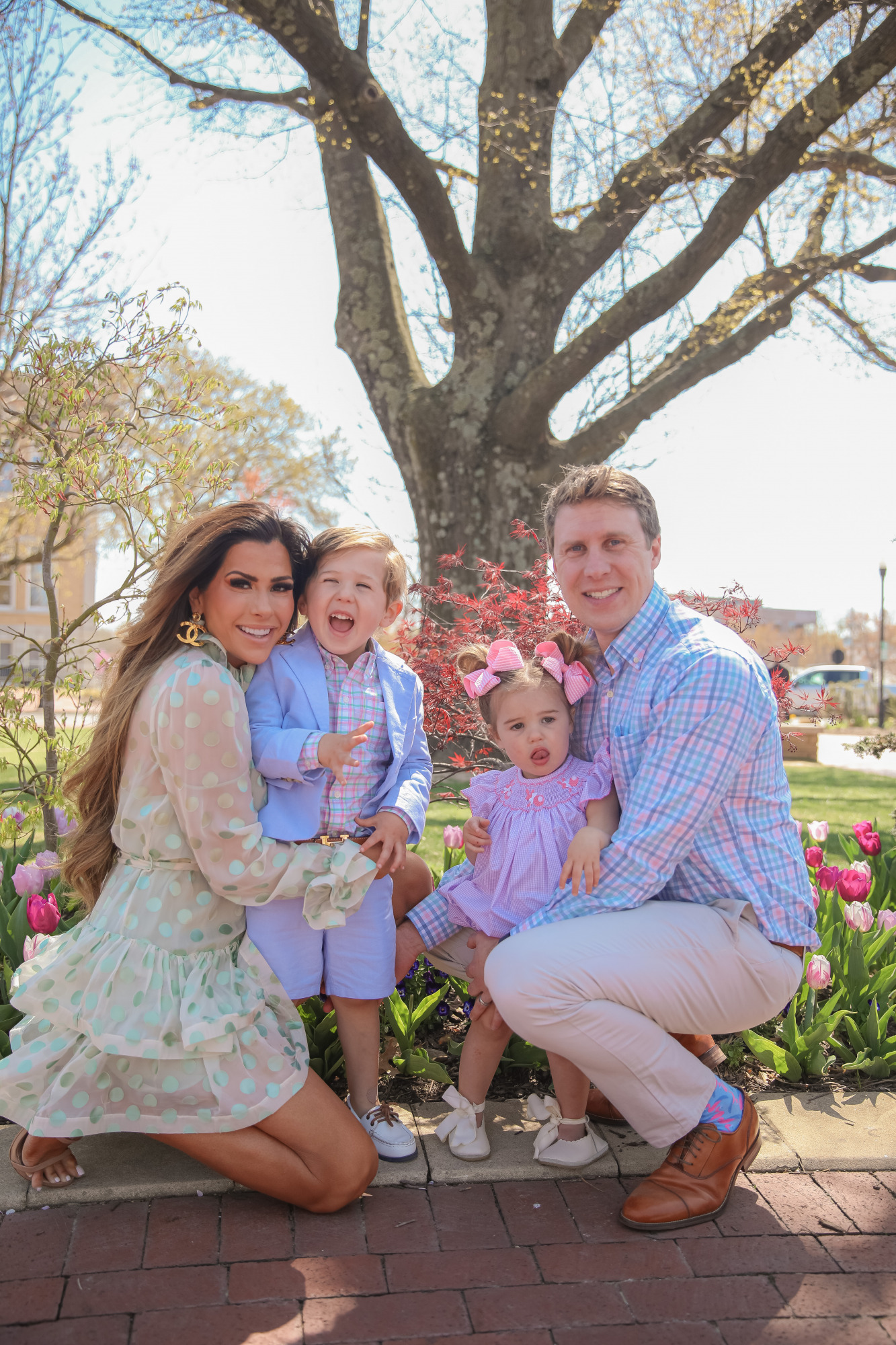 Zimmermann dress, family easter outfit photos, toddler fashion outfit spring summer 2021, Emily Gemma   April Instagram Recap by popular US fashion blog, The Sweetest Thing: image of Emily Gemma, her two kids and her husband kneeling together outside and wearing a cream and blue polka dot print dress, pink and blue plaid button up shirt, tan slacks, pink dress, pink hair bows, blue blazer, blue shorts, and white boater shoes.