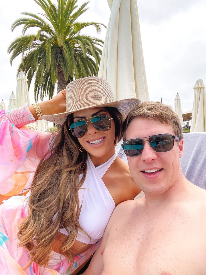 Couple hanging out by the pool, Emily Gemma, John Gemma, Straw beach hat, white swimsuit, white bikini top, saint laurent sunglasses, colorful swim cover up, laguna beach | Instagram Recap by popular US life and style blog, The Sweetest Thing: image of Emily Gemma sitting on a lounge chair at the beach and wearing aviator sunglasses, straw hat, white two piece swimsuit and pink tropical print chiffon coverup.