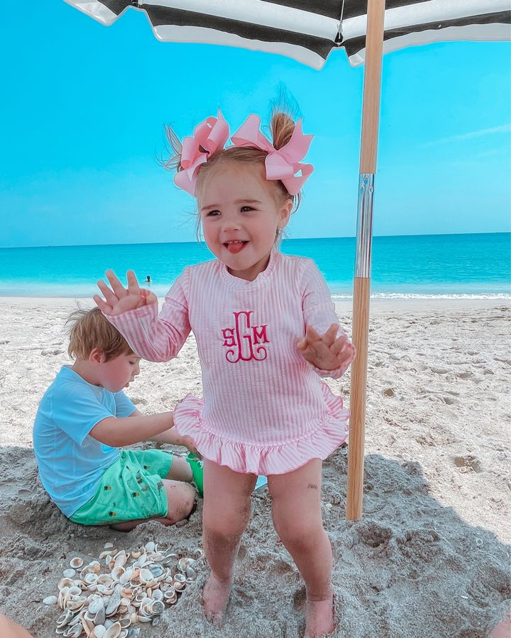 Sophie Gemma, Luke Gemma, Swim wear, Toddler Swim Suits, Monogrammed Swimsuit, Beachwear, Emily Gemma   April Instagram Recap by popular US fashion blog, The Sweetest Thing: image of a young boy and girl playing in the sand under a black and white stripe shad umbrella and wearing pink hair bows, pink and white stripe monogram Smock Auctions swimsuit, white rash guard, and green swim shorts.