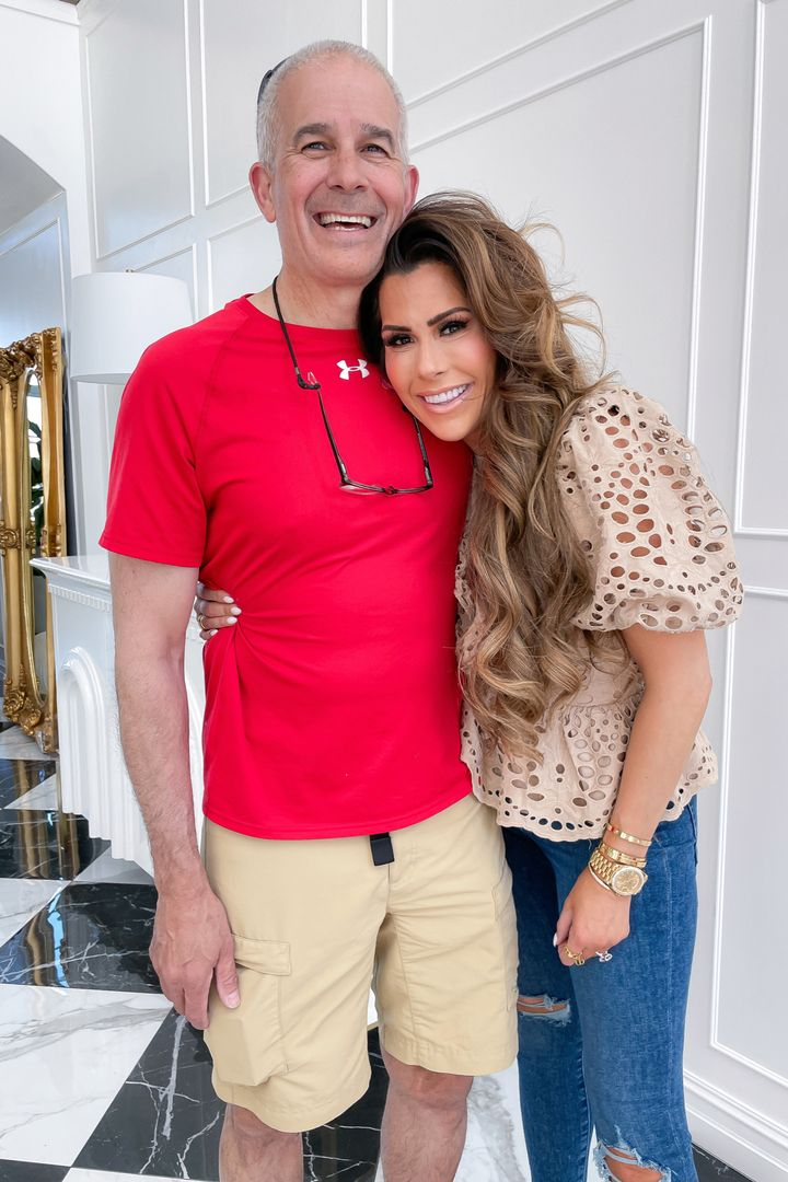 Express top ideas, Emily Ann Gemma, tan blouse and jeans with rips in the knees, casual spring outfit ideas 2021, affordable outfit ideas, designer look alike fashion | Instagram Recap by popular US life and style blog, The Sweetest Thing: image of Emily Gemma wearing a tan eyelet puff sleeve top and distressed jeans and standing with her arm around her dad.