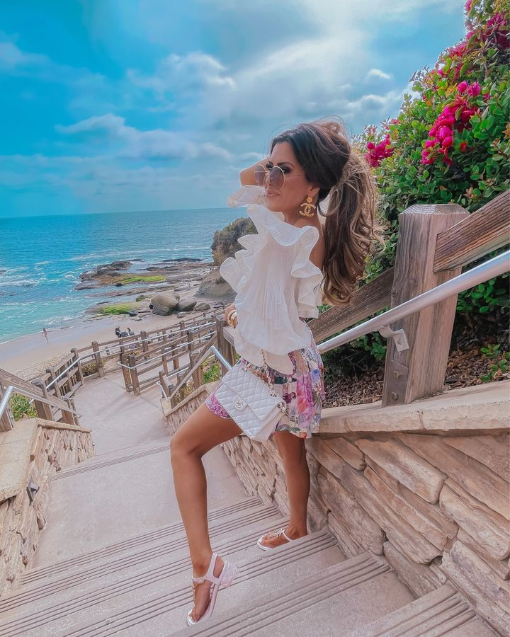 Zimmermann top, Cettire, Chanel pink sandals, Emily Ann Gemma, Ruffle long sleeve crop top, dior round sunglasses, high ponytail, laguna montage , chanel earrings | Instagram Recap by popular US life and style blog, The Sweetest Thing: image of Emily Gemma standing on some cement stairs near the ocean and wearing a white long sleeve crop top, gold Chanel statement earrings, round sunglasses, floral print shorts, white sandals, and holding a white quilted purse.
