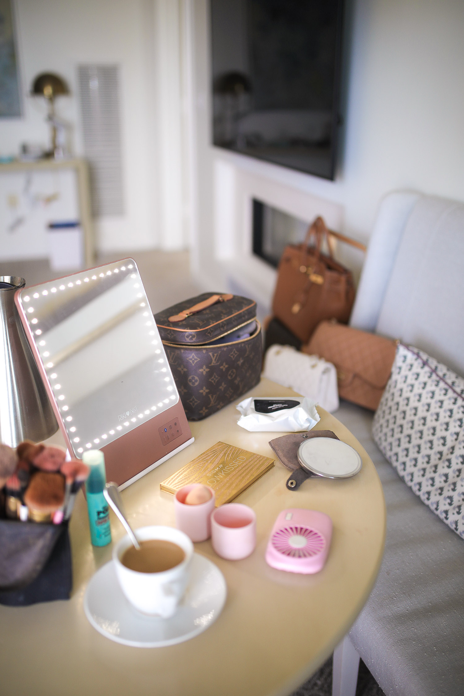 Riki Size Travel Mirror, pink travel fan makeup, beauty sponge holder travel amazon, Louis Vuitton Nice Case, Emily Gemma | Travel Hacks by popular life and style blog, The Sweetest Thing: image of a makeup mirror, Louis Vuitton makeup bag, makeup brush holder, cup of coffee, portable hand fan, beauty blender, and makeup pallet.