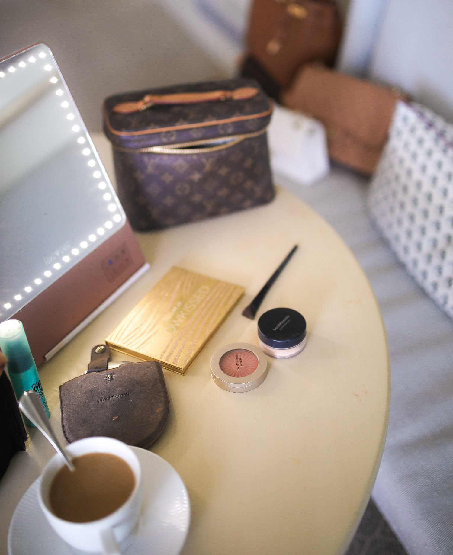 Bare minerals triangle makeup brush, best makeup brush for undereye concealer, amazon makeup travel must haves | Travel Hacks by popular life and style blog, The Sweetest Thing: image of a makeup mirror, Louis Vuitton makeup bag, makeup pallet, makeup brush and blush.