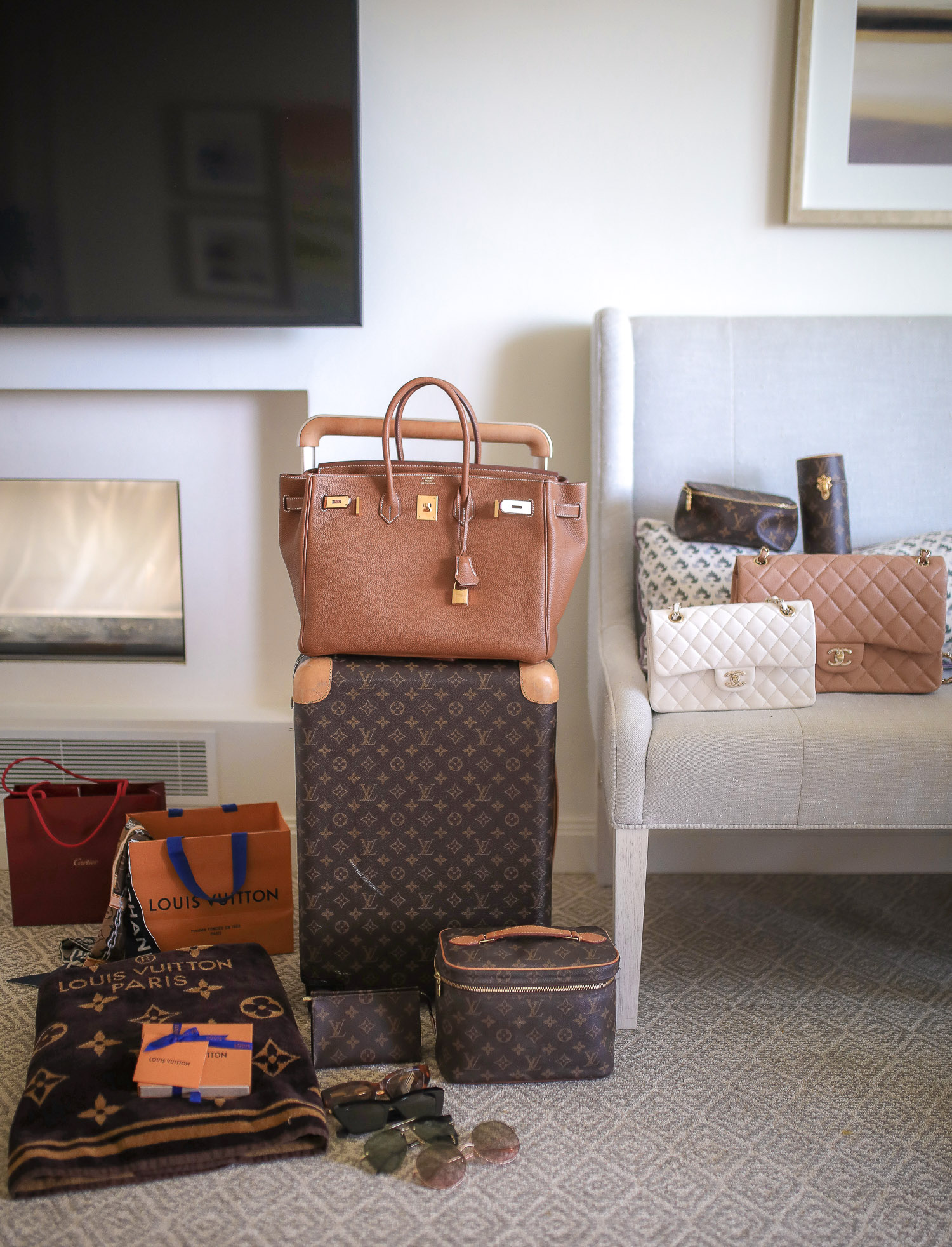 Louis Vuitton Horizon 55 carry on, Hermes berkin 35 tan gold hardware, Louis Vuitton beach towel, Emily Gemma | Travel Hacks by popular life and style blog, The Sweetest Thing: image of Louis Vuitton luggage, Louis Vuitton blanket, Louis Vuitton makeup bag, Chanel purses, and designer sunglasses.