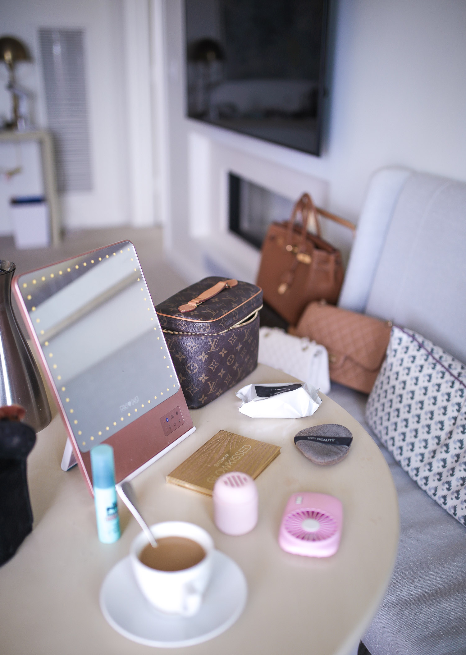 Riki Size Travel Mirror, pink travel fan makeup, beauty sponge holder travel amazon, Louis Vuitton Nice Case, Emily Gemma | Travel Hacks by popular life and style blog, The Sweetest Thing: image of a makeup mirror, Louis Vuitton makeup bag, portable fan, and cup of coffee.