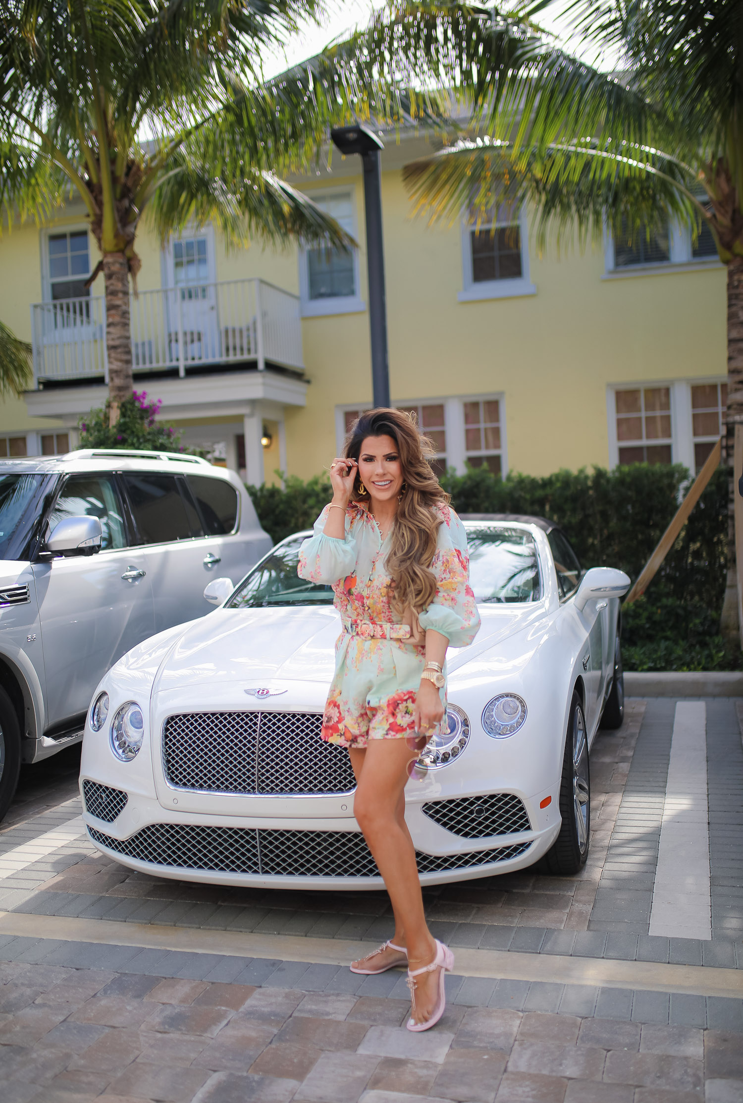 Palm beach where to stay, White elephant palm beach, Zimmerman Mae Floral Shorts and Blouse, Tiktok viral jewelry anklet, Amazon Tiktok Viral anklet, Chanel Large Button Paris Gold earrings, high end fashion blog, Emily gemma, the sweetest thing blog, luxury travel blog, palm beach white elephant | Zimmermann Outfit by popular US fashion blog, The Sweetest Thing: image of Emily Gemma standing by a white Bentley and wearing a Zimmerman Mae Floral Shorts and Blouse, Tiktok viral jewelry anklet, Amazon Tiktok Viral anklet, Chanel Large Button Paris Gold earrings, Cartier bracelets, gold Rolex watch, Chanel sandals and carrying a Chanel handbag.