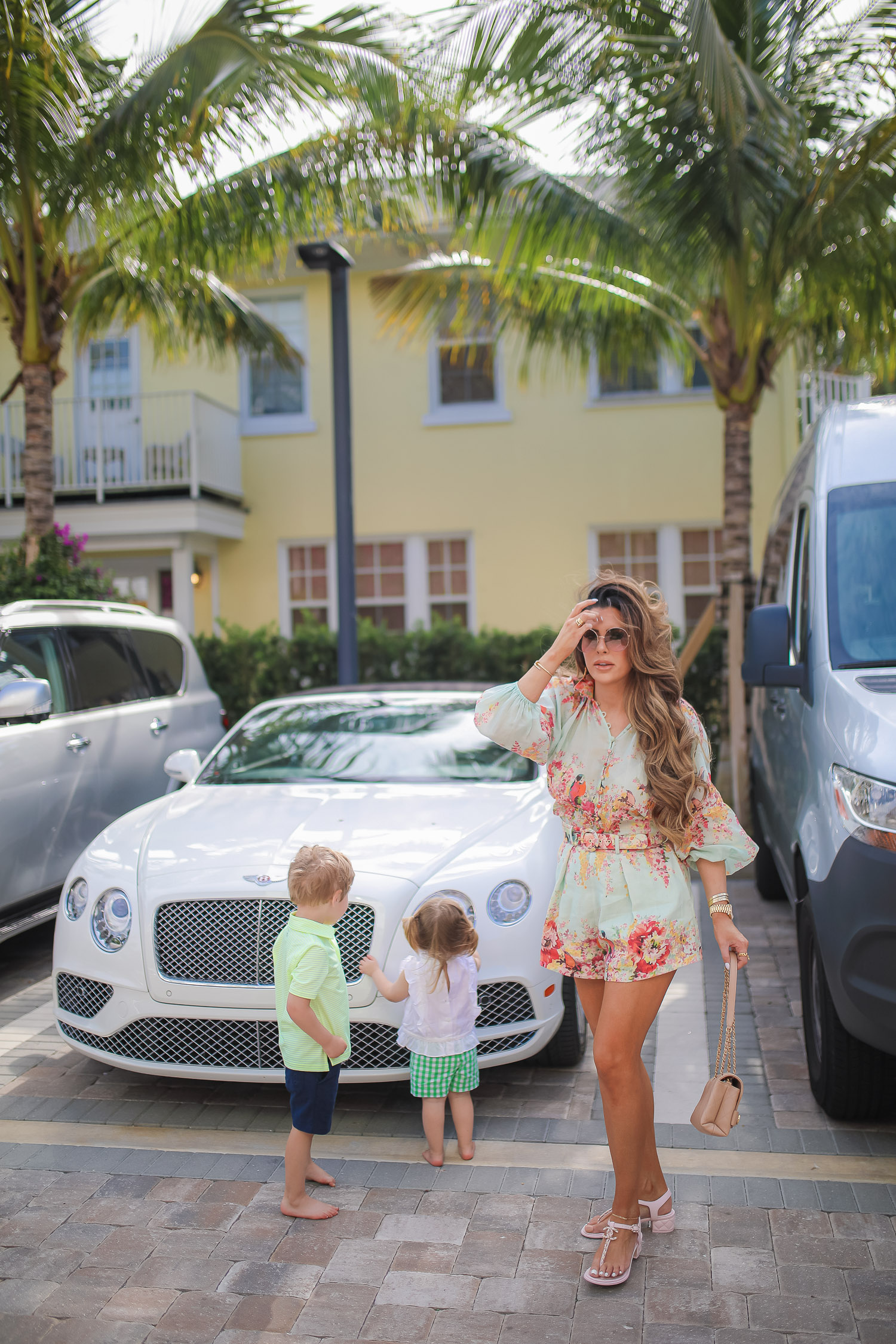Palm beach where to stay, White elephant palm beach, Zimmerman Mae Floral Shorts and Blouse, Tiktok viral jewelry anklet, Amazon Tiktok Viral anklet, Chanel Large Button Paris Gold earrings, high end fashion blog, Emily gemma | Zimmermann Outfit by popular US fashion blog, The Sweetest Thing: image of Emily Gemma standing with her kids by a white Bentley and wearing a Zimmerman Mae Floral Shorts and Blouse, Tiktok viral jewelry anklet, Amazon Tiktok Viral anklet, Chanel sandals, Chanel Large Button Paris Gold earrings, Cartier bracelets, gold Rolex watch, and carrying a Chanel handbag.