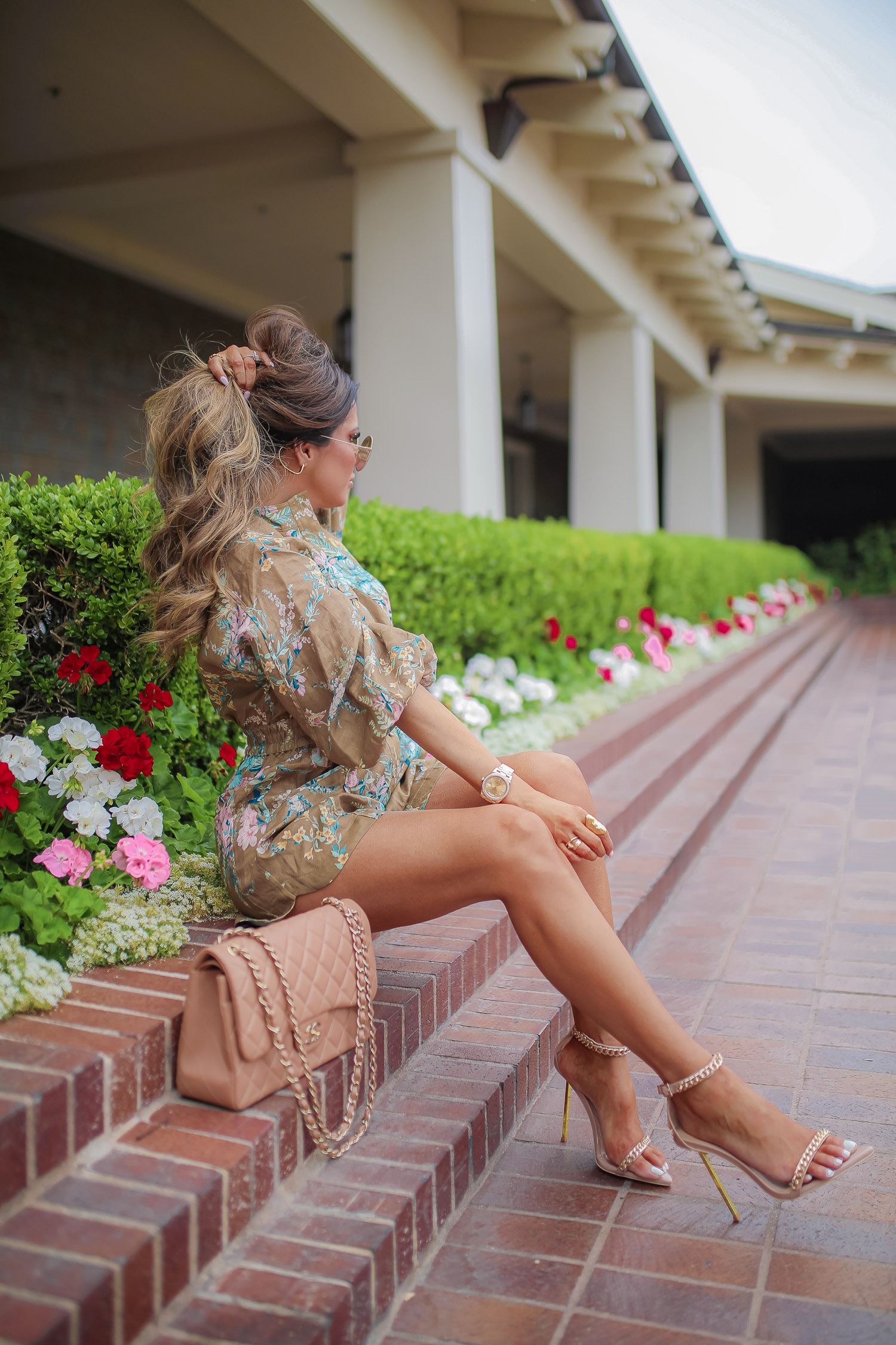 Zimmerman-floral-utility-romper-jessica-rich-heels-laguna-beach-montage-emily-gemma-cute-rompers-spring-2021-pinterest-summer-fashion-2021 | Instagram Recap by popular US life and style blog, The Sweetest Thing: image of Emily Gemma sign on some brick steps next to some green bushes and red, white and pink flowers and wearing a brown floral print utility rompers and tan gold chain strap stiletto heel sandals.