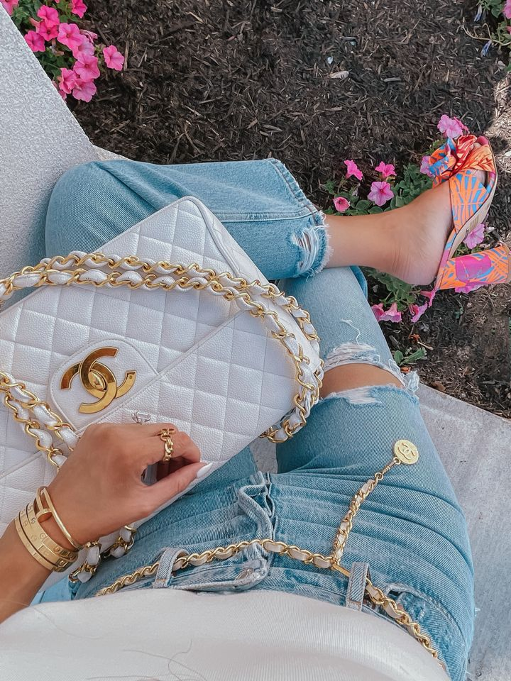 white chanel handbag, white and gold chanel handbag, tropical bright colored heels, cropped jeans, cream color bodysuit, vintage chanel belt, Emily Ann gemma, warm weather outfit ideas, summer outfit ideas 2021 | Instagram Recap by popular US life and style blog, The Sweetest Thing: image of Emily Gemma wearing tropical print black heel sandals, light wash distressed high waist denim and holding a white quilted Chanel handbag.