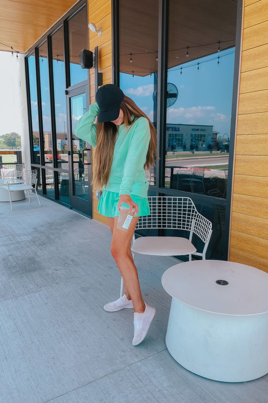 workout outfit, emily ann gemma, errand outfit, free people shorts, Zella sweatshirt, Lululemon baller cap, apl tennis shoes, best athletic shoes, best athletic outfits, Emily ann gemma, summer 2021 | June Instagram Recap by popular US fashion blog, The Sweetest Thing: image of Emily Gemma wearing a black hat, mint green long sleeve top, mint green skirt, and white sneakers.
