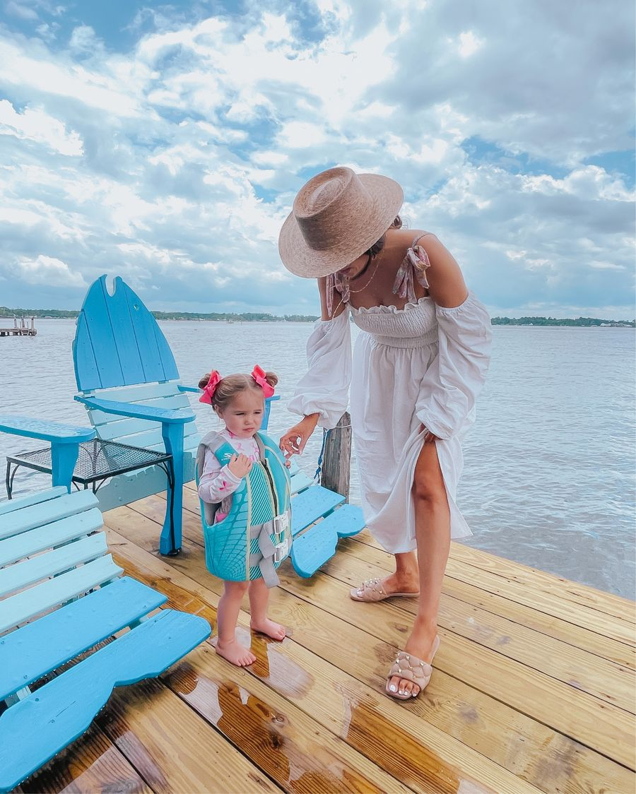 summer outfit ideas 2021, best swimsuits, floral swimsuit, affordable swim cover up, best summer sandals, nude sandals, valentine dupe sandals, best summer hats, Emily ann gemma | June Instagram Recap by popular US fashion blog, The Sweetest Thing: image of Emily Gemma and her daughter Sophie standing on a pier next to some blue wooden chairs shaped like fish.