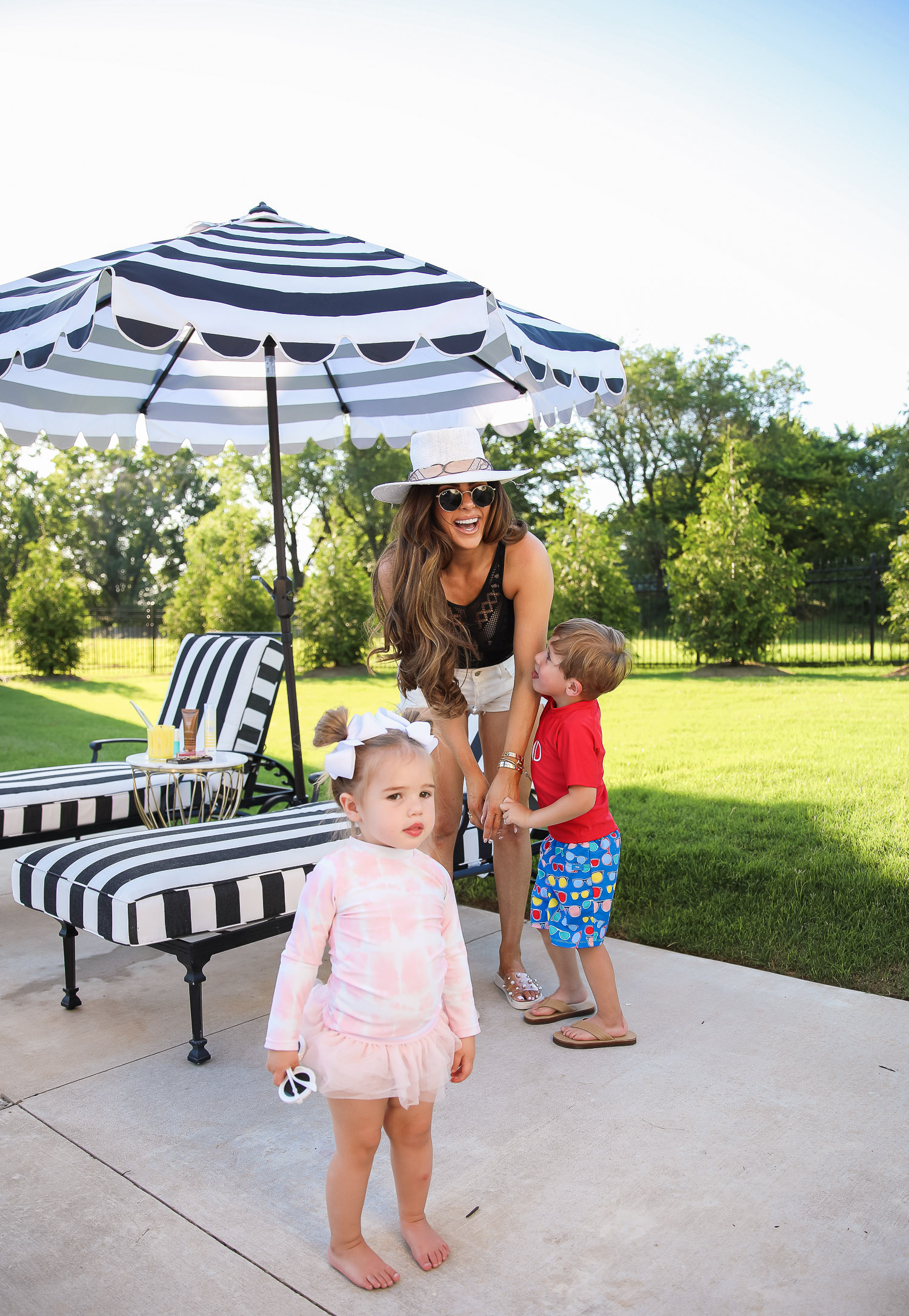 Becca-black-swimsuit-nordstrom-target-marble-gold-outdoor-table-emily-gemma-backyard-pinterest-backyard-inspiration | June Instagram Recap by popular US fashion blog, The Sweetest Thing: image of Emily Gemma standing outside with her young son and daughter next to her black and white stripe shade umbrella and lounge chairs with black and white stripe cushions.