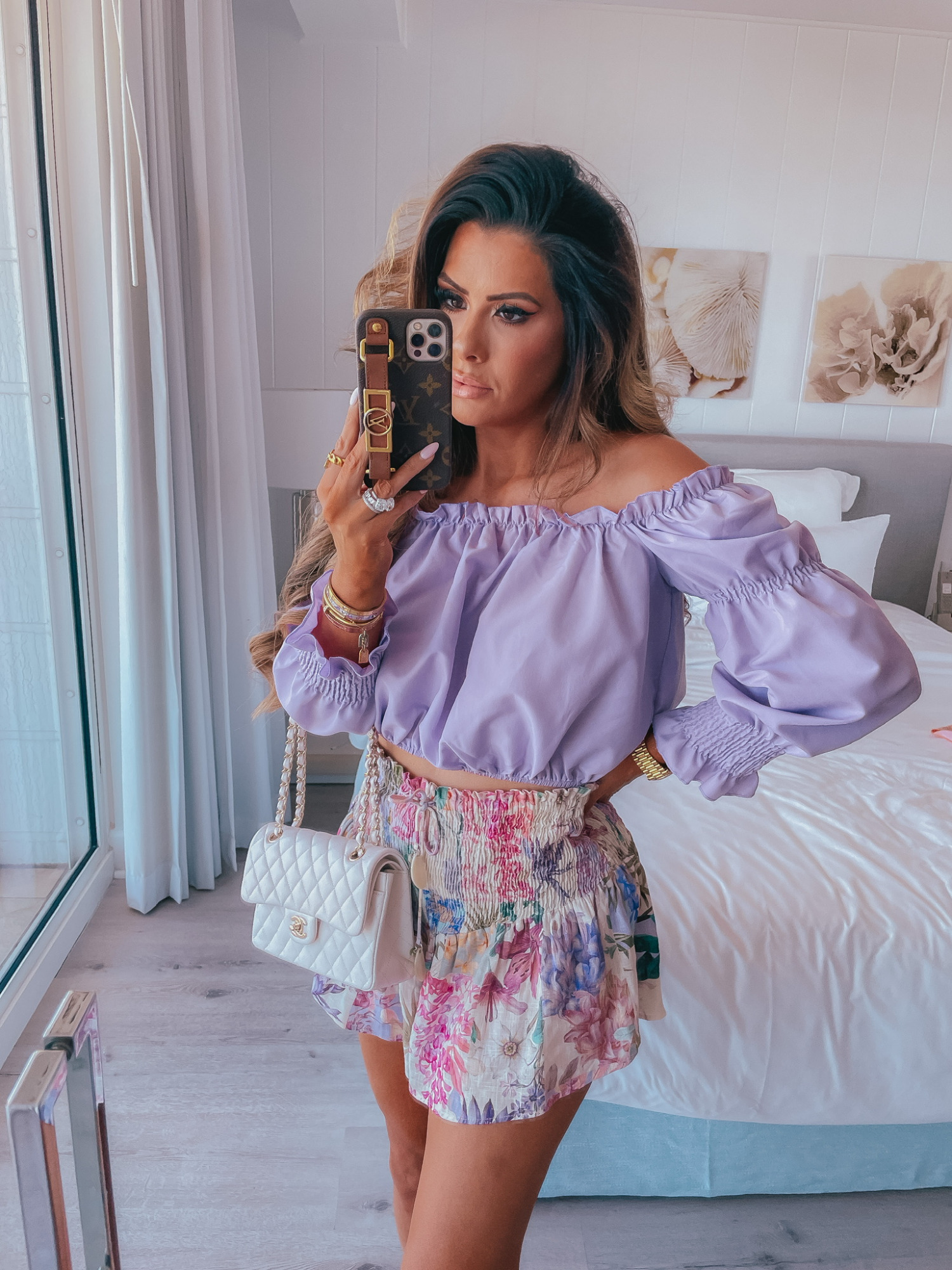 Purple off the shoulder top, nasty gal top, white chanel handbag, floral shorts with elastic waistband, Emily Ann gemma, Louis Vuitton phone case, beach outfit ideas | Instagram Recap by popular US life and style blog, The Sweetest Thing: image of Emily Gemma wearing a purple off the shoulder long sleeve top, white floral print shorts and holding a white quilted handbag.